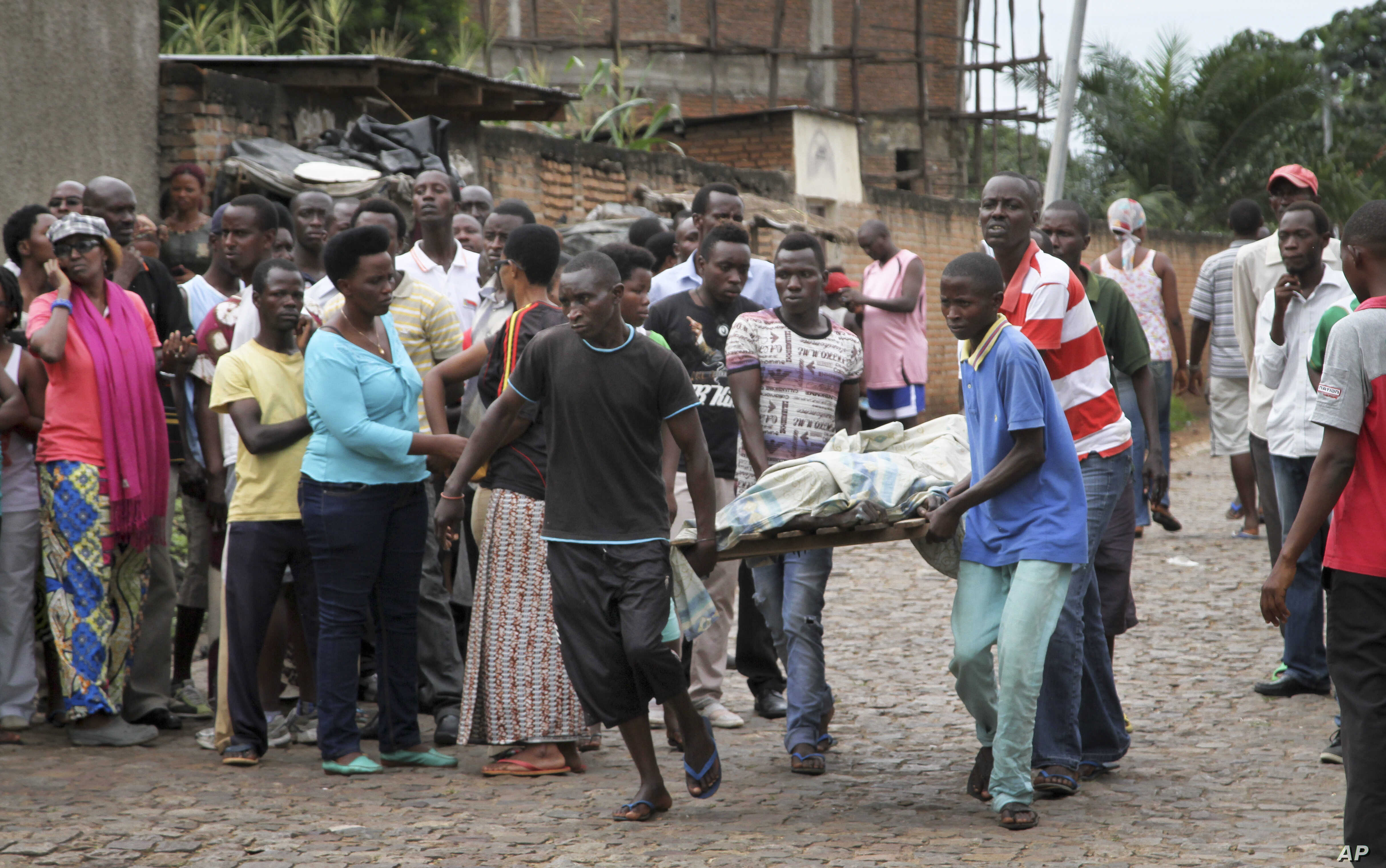 Men carry away a dead body in the Nyakabiga neighborhood of Bujumbura, Burundi, where a number of people were found shot dead a day after the government said an unidentified group had carried out coordinated attacks on three military installations, D...