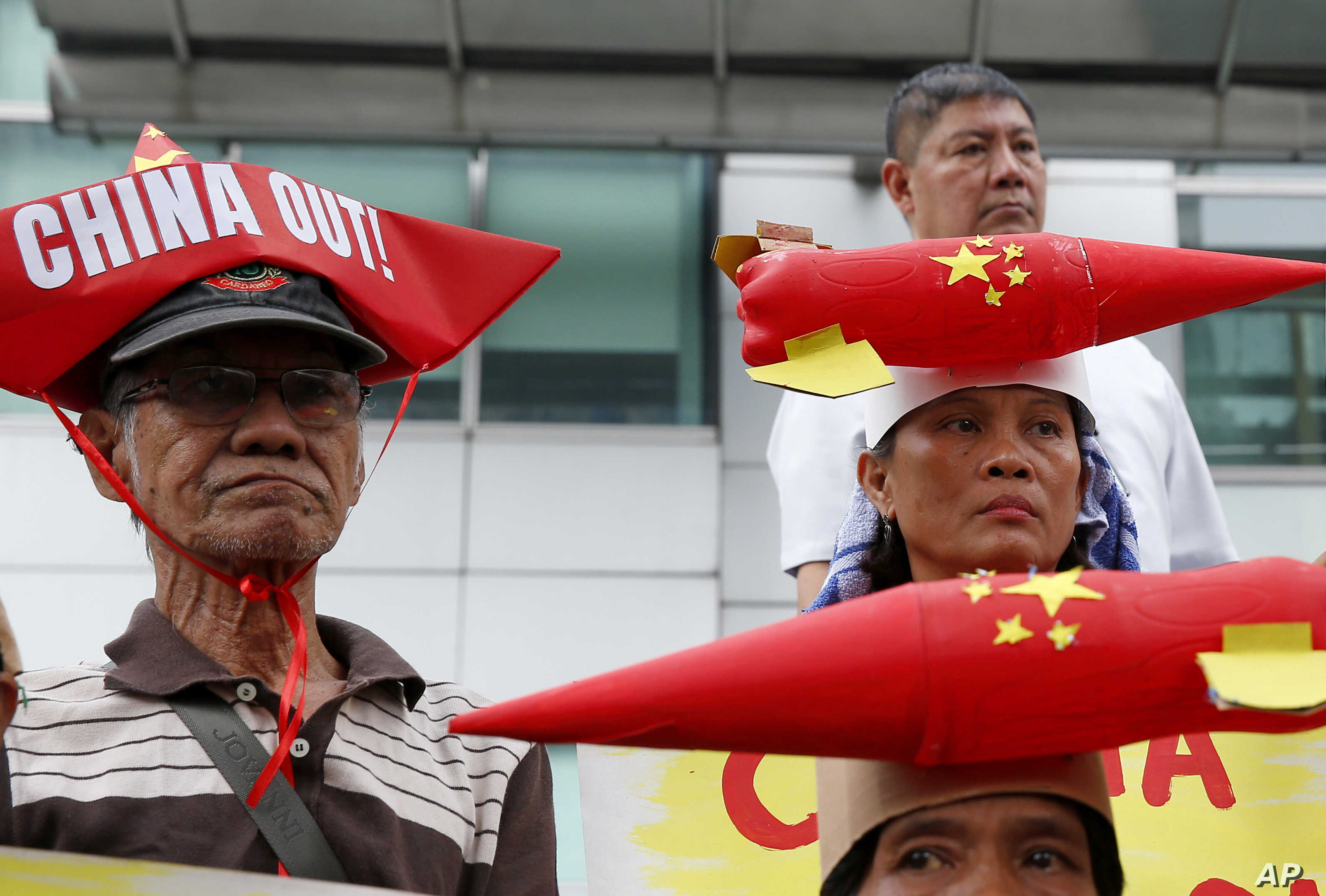 Protesters, wearing boat-shaped paper hats and mock missiles, join others in a rally at the Chinese Consulate to protest China's alleged continued militarization of the disputed islands in the South China Sea known as Spratlys, Feb. 10, 2018, in Maka...