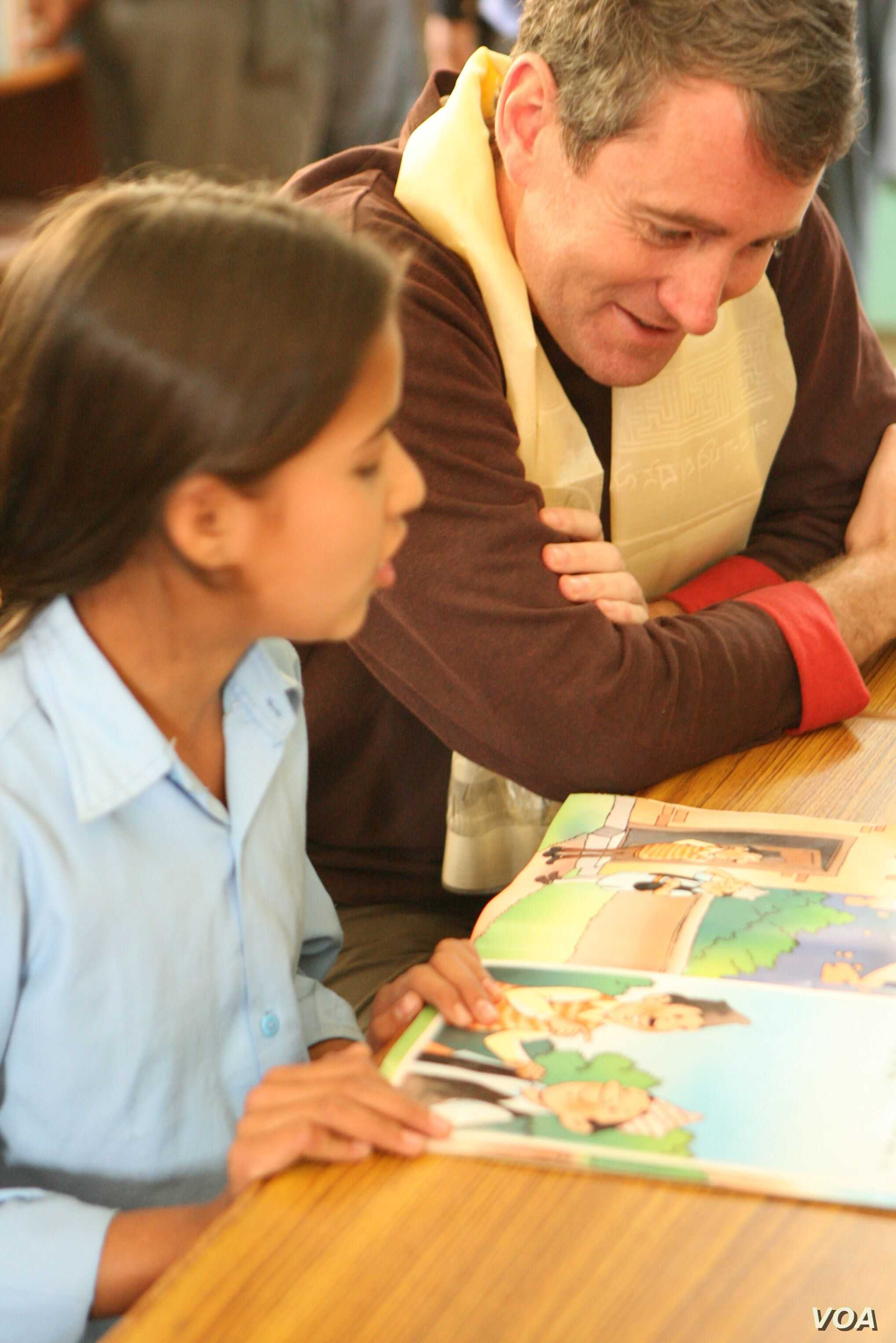 Room to Read founder John Wood reads to a girl in Nepal. (Andrea McTamaney)