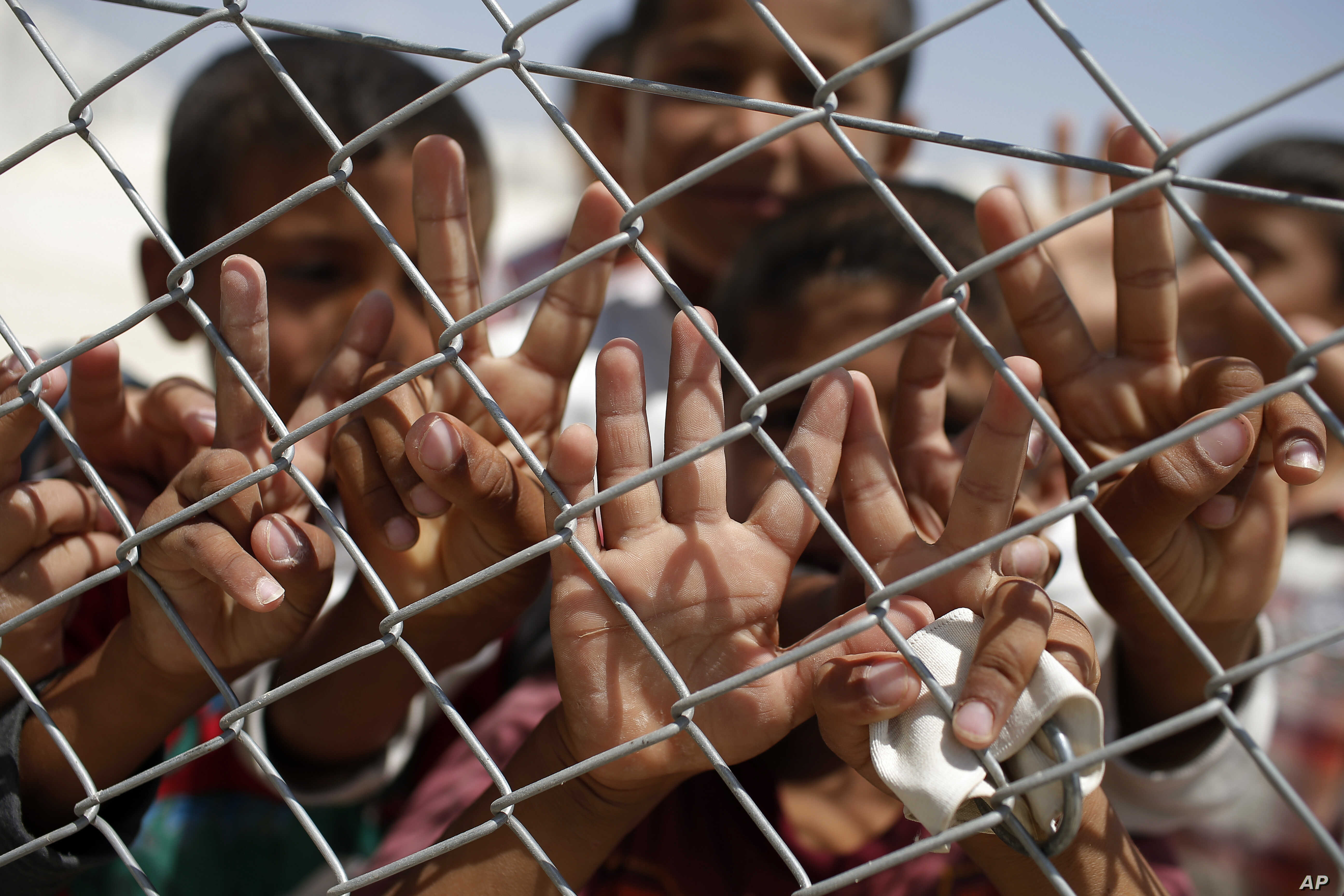 FILE - Syrian refugee children wave and flash the V-sign at a refugee camp in Suruc, on the Turkey-Syria border, June 19, 2015.