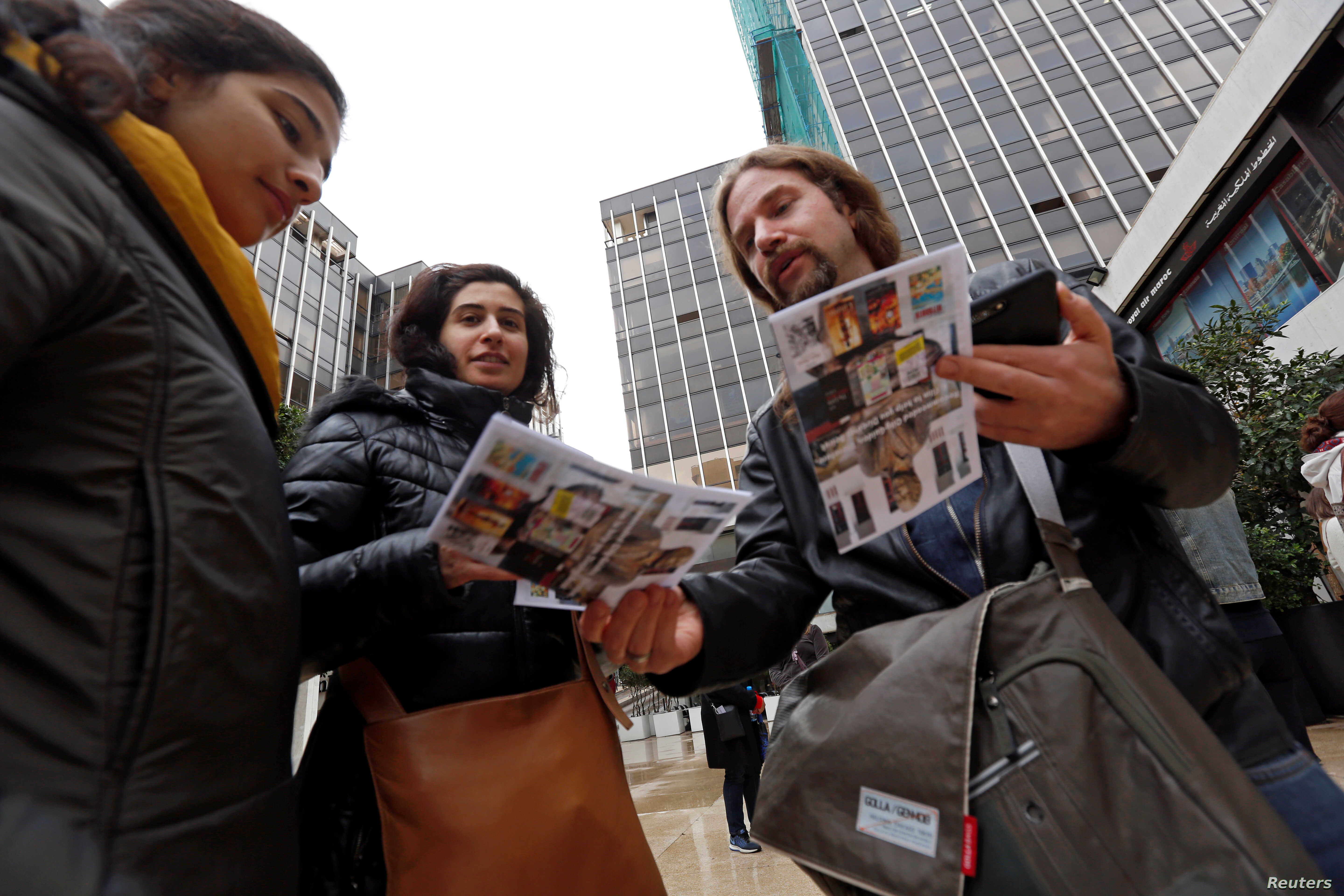 Tour guide Ronnie Chatah, 36, gives the tour brochures to visitors in Beirut, Lebanon, Jan. 28, 2018.