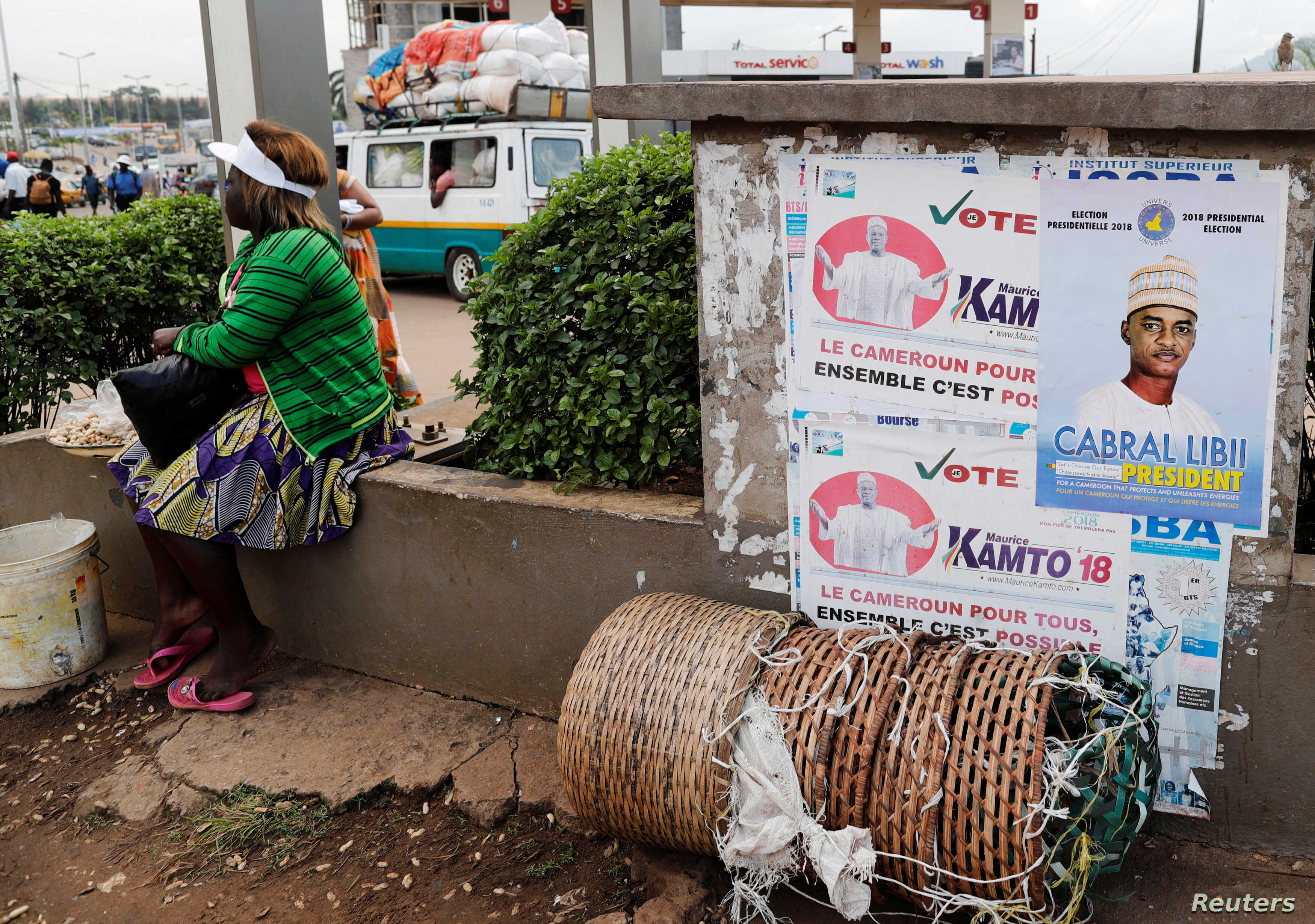 A street vendor sits near placards of presidential candidates Cabral Libii (R) of Univers party and Maurice Kamto of the Movement for Renaissance, in Yaounde, Cameroon, Oct. 5, 2018.