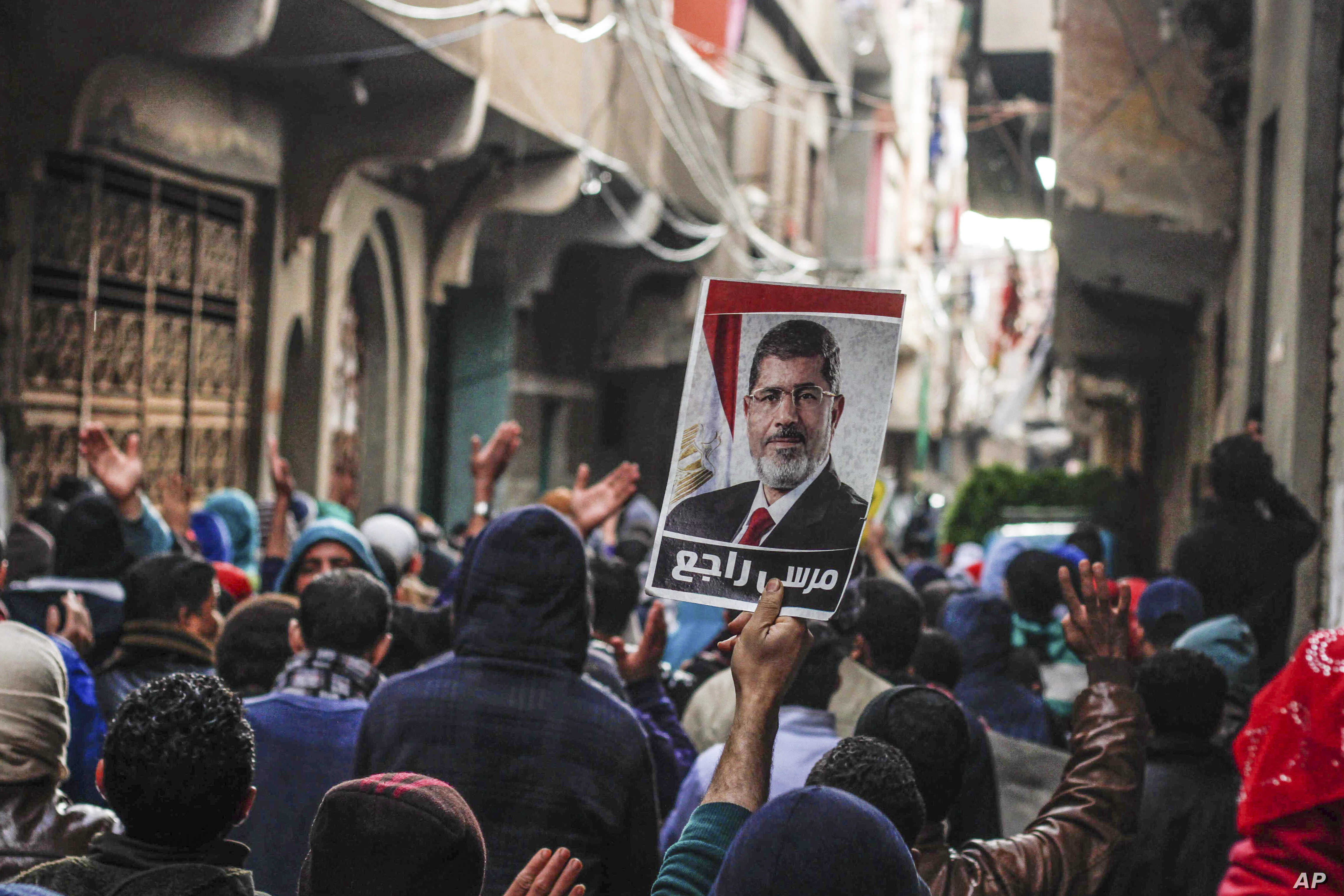 FILE - supporters of ousted Islamist President Mohamed Morsi, chant slogans and raise an image of him after the Muslim Brotherhood called on its supporters to take to the streets on the anniversary of the 2011 uprising, in Cairo, Egypt.