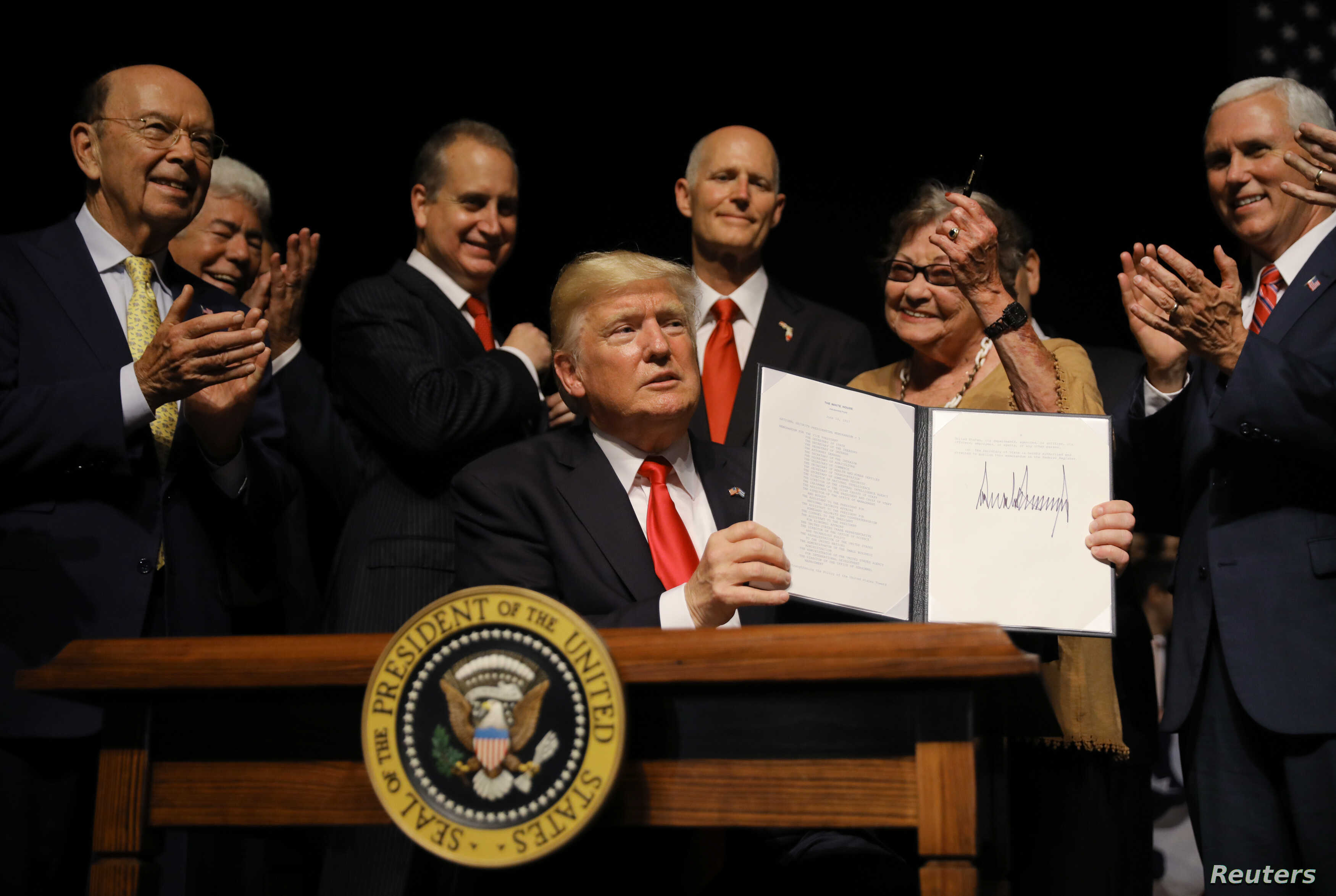 U.S. President Donald Trump is applauded after signing an Executive Order on US-Cuba policy at the Manuel Artime Theater in Miami, Florida, U.S
