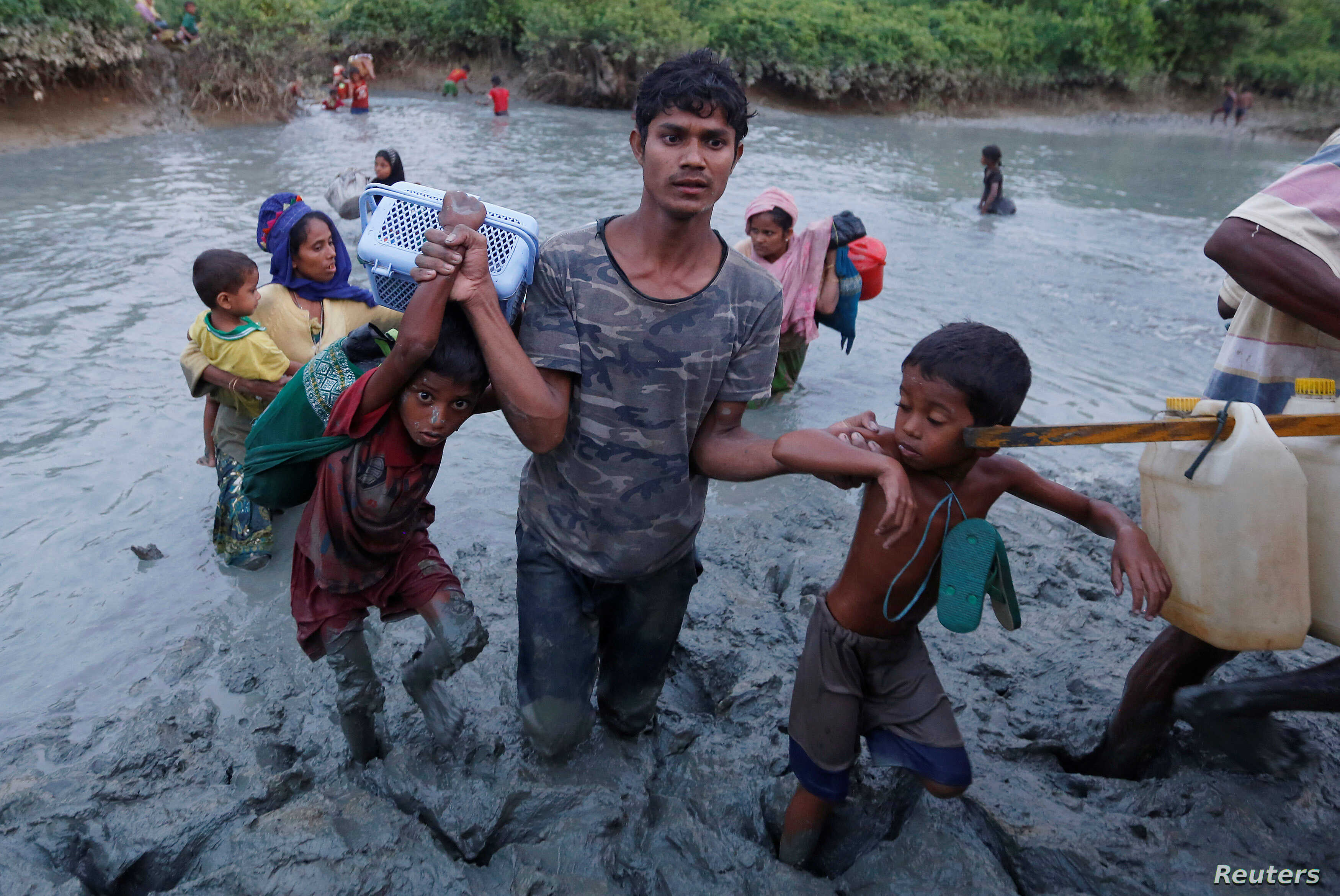 A Rohingya refugee man helps children through the mud after crossing the Naf River at the Bangladesh-Myanmar border in Palong Khali, near Cox's Bazar, Bangladesh, Nov. 1, 2017.
