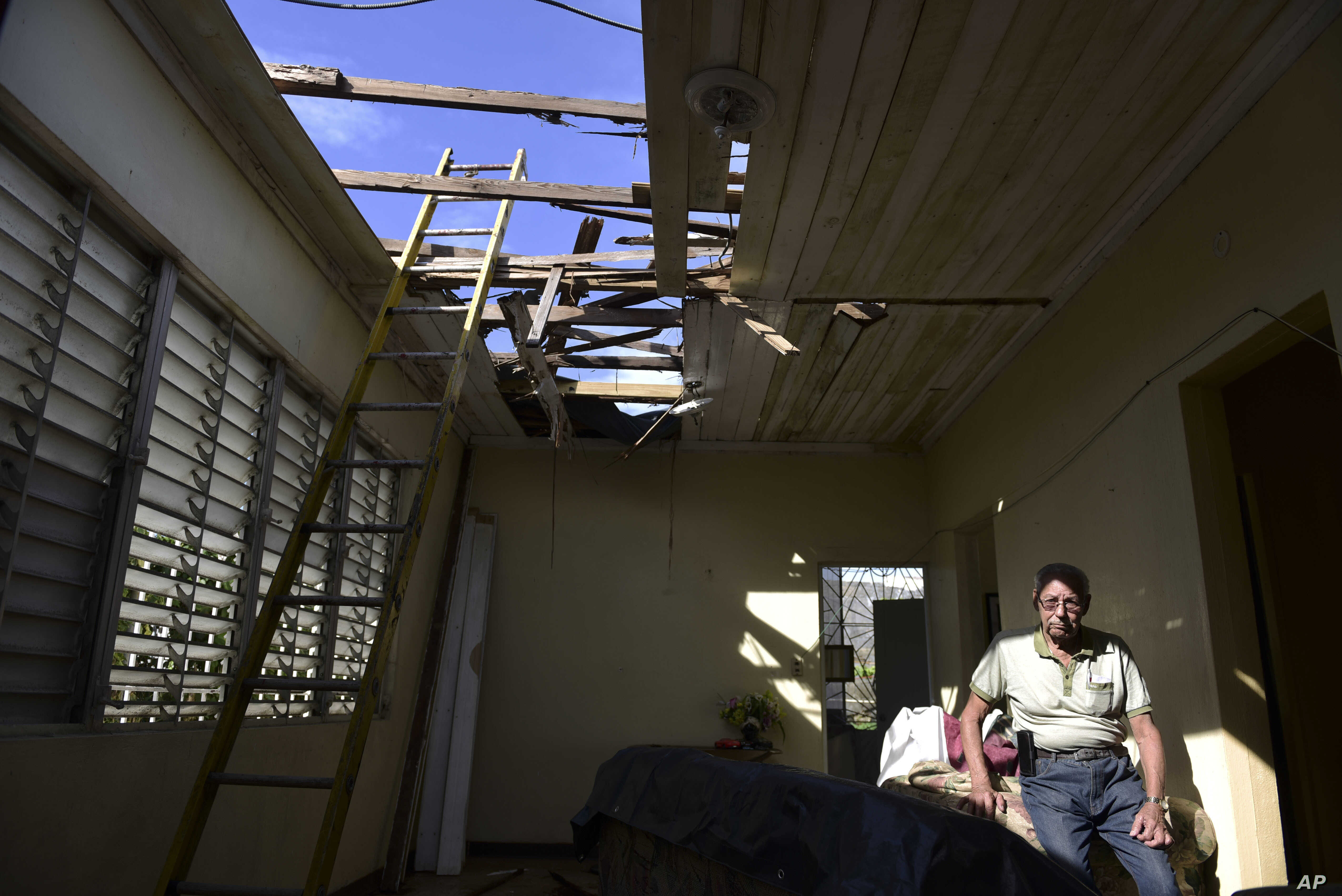 In this Nov. 15, 2017 photo, Edgardo de León sits in his living room with a hole in the ceiling caused by Hurricane Maria, in Cataño, Puerto Rico.