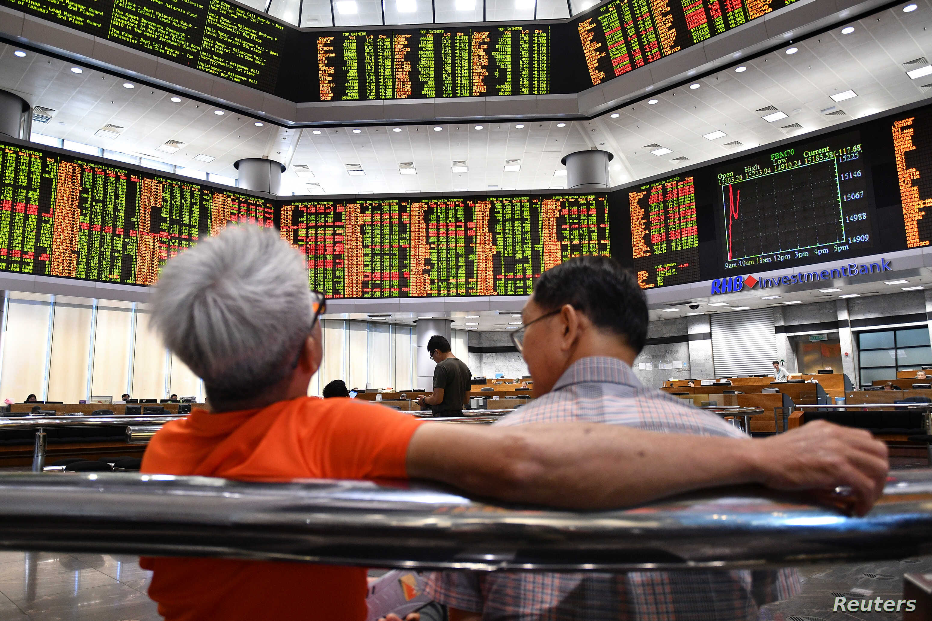 People look at trading boards at a private stock market gallery in Kuala Lumpur, Malaysia, May 14, 2018.