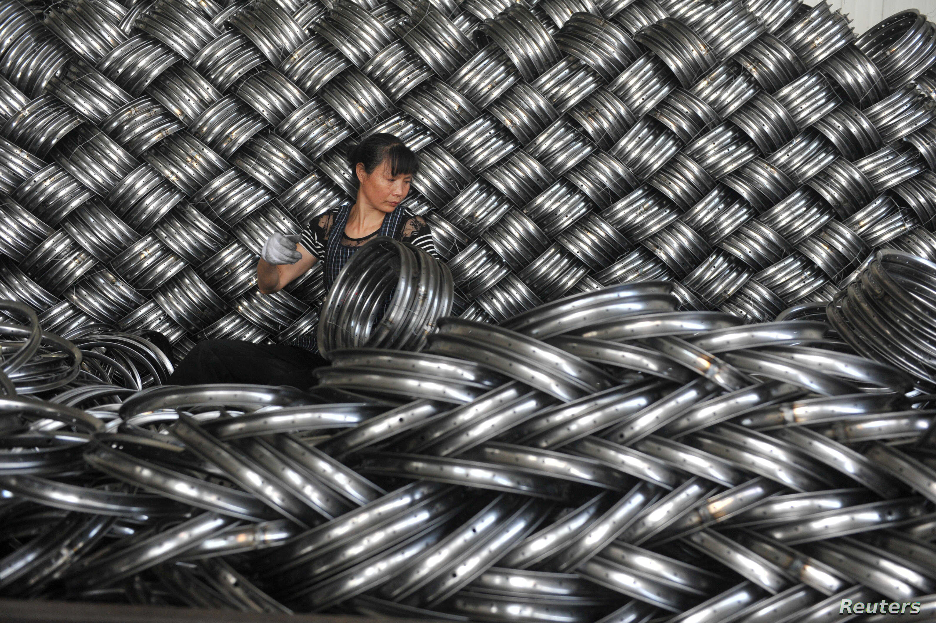FILE - A woman works on packaging bicycle rim steels for export at a workshop of a company manufacturing sports equipments in Hangzhou, Zhejiang province, China, June 4, 2018.