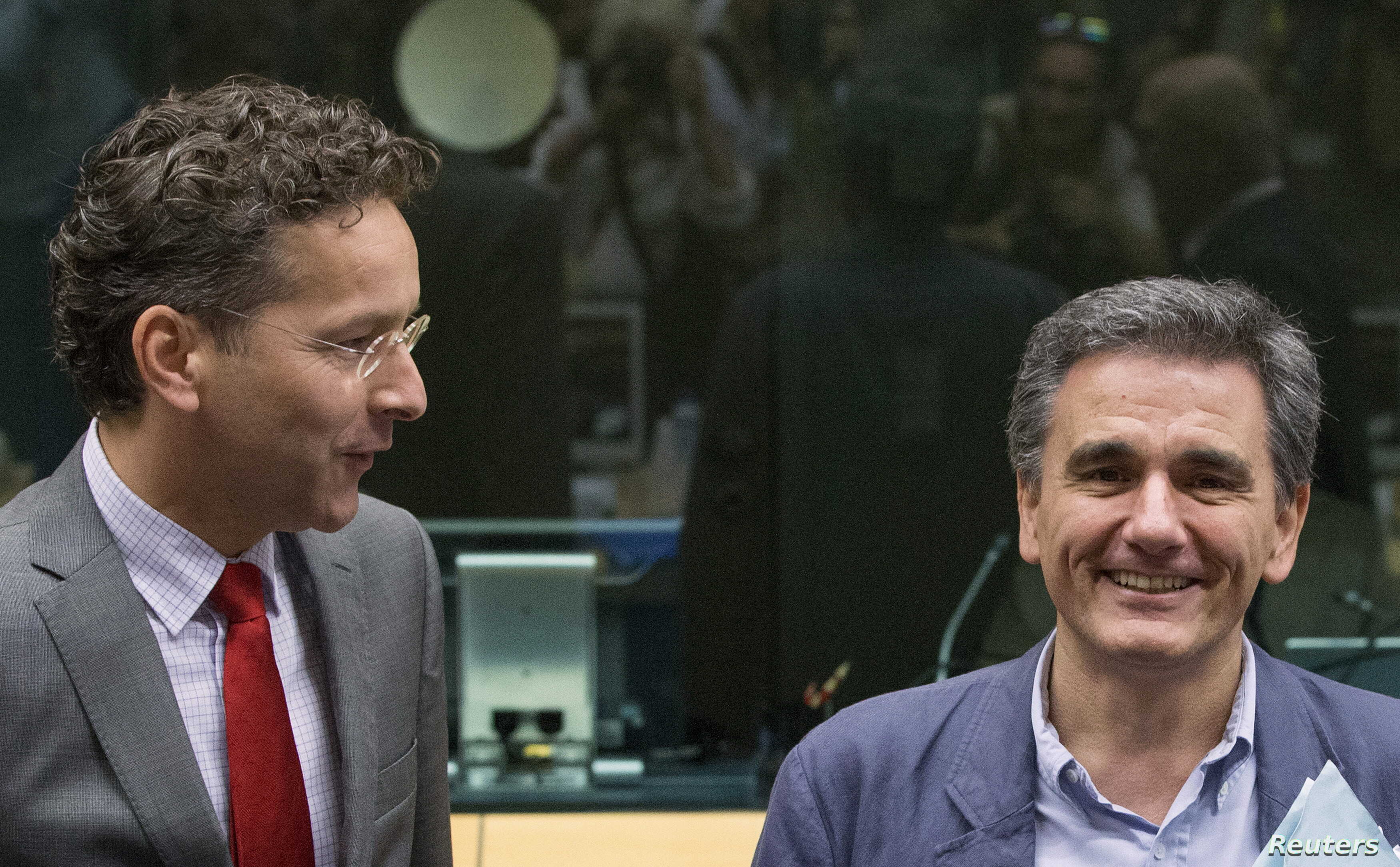 Newly appointed Greek Finance Minister Euclid Tsakalotos (R) is welcomed by Eurogroup President Jeroen Dijsselbloem (L) at a euro zone finance ministers meeting on the situation in Greece in Brussels, Belgium, July 7, 2015.