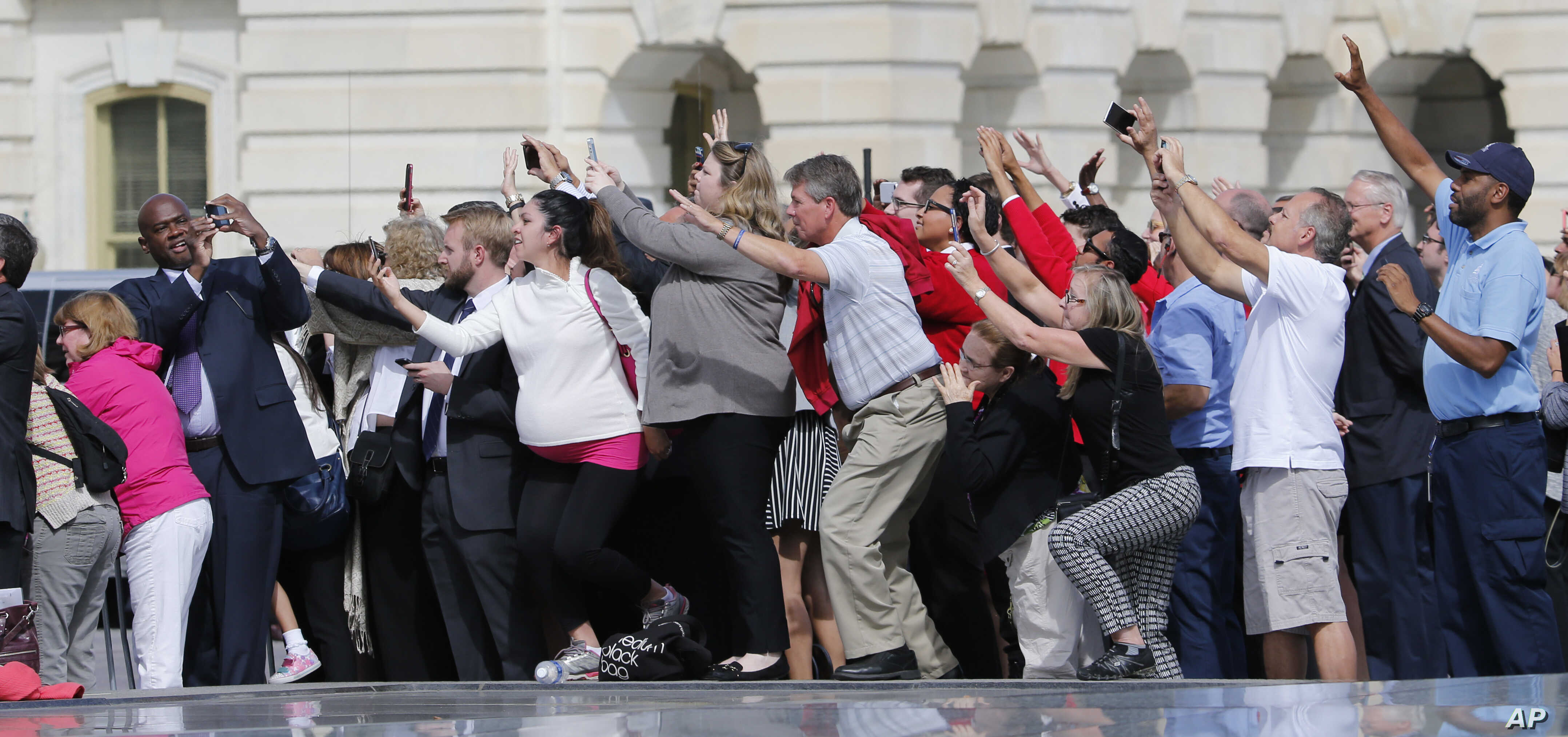 Congressional staffers and guests strain to view and photograph the departure of Pope Francis in his Fiat 500L, on Capitol Hill in Washington after his speech before a joint meeting of Congress, Sept. 24, 2015.