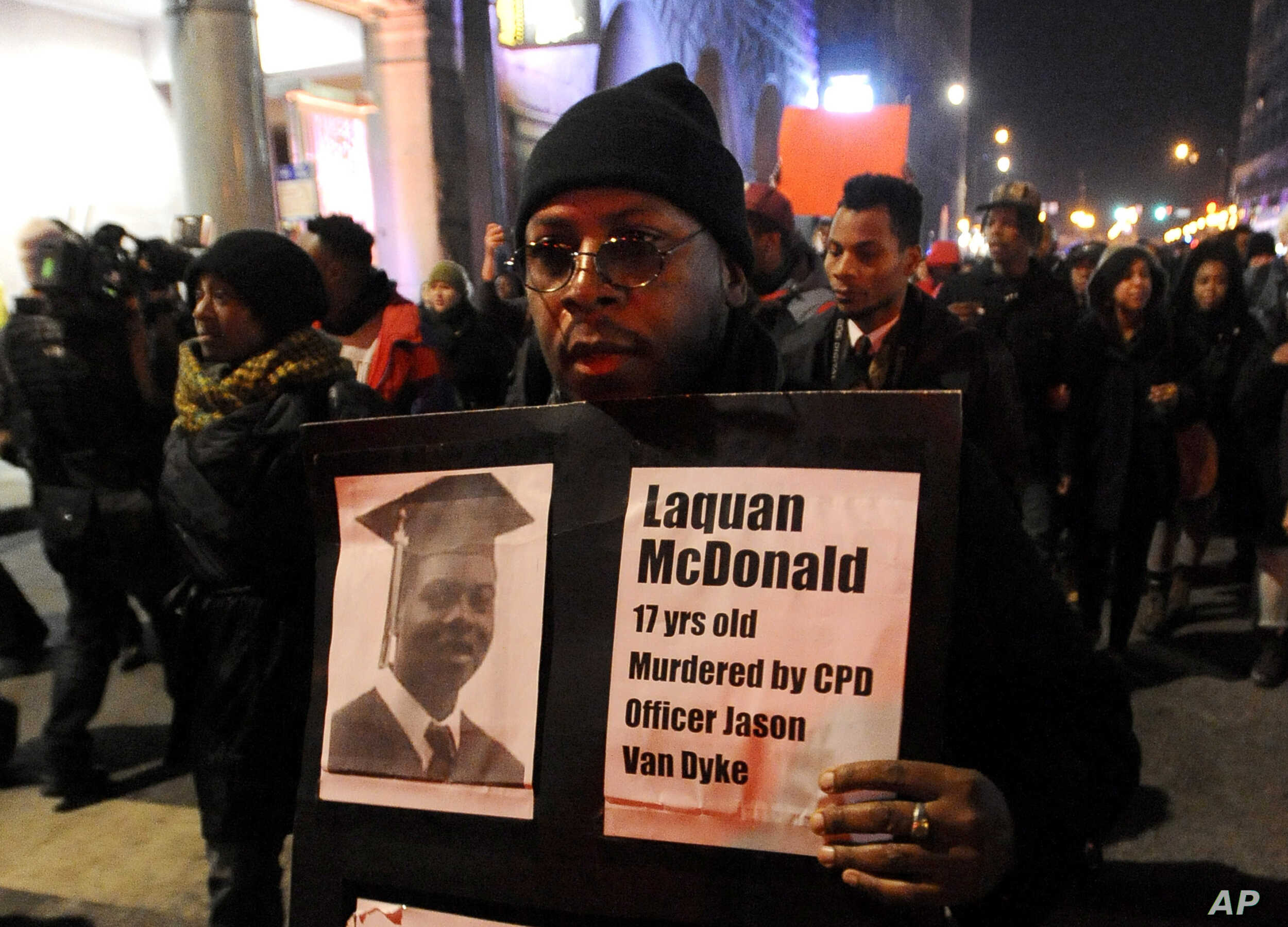 A protester holds a sign as people rally in memory of 17-year-old Laquan McDonald, who was shot 16 times by Chicago Police Department Officer Jason Van Dyke, in Chicago,  Nov. 24, 2015.