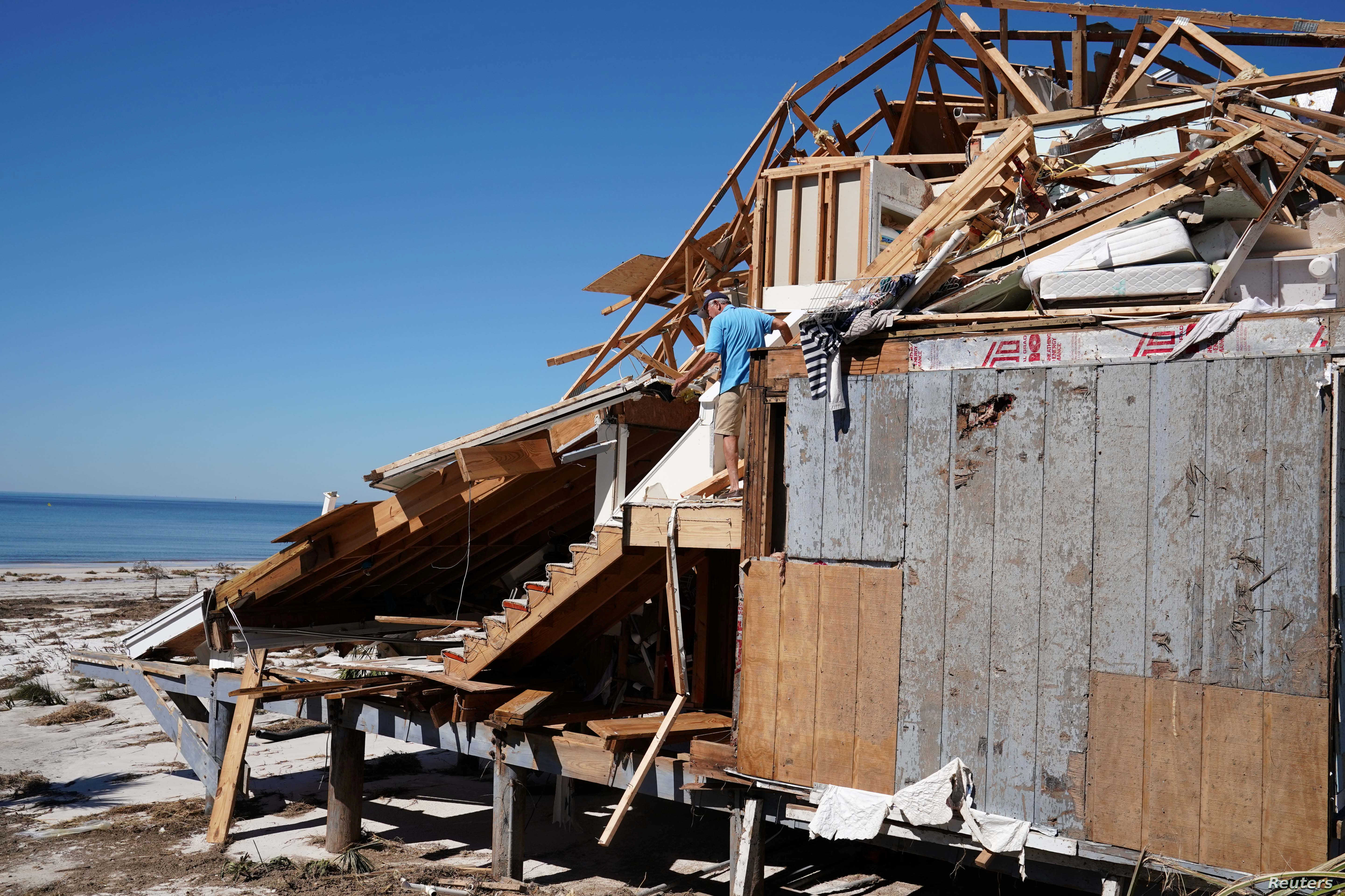 People clean up their house that was destroyed by Hurricane Michael in Mexico Beach, Fla., Oct. 13, 2018.