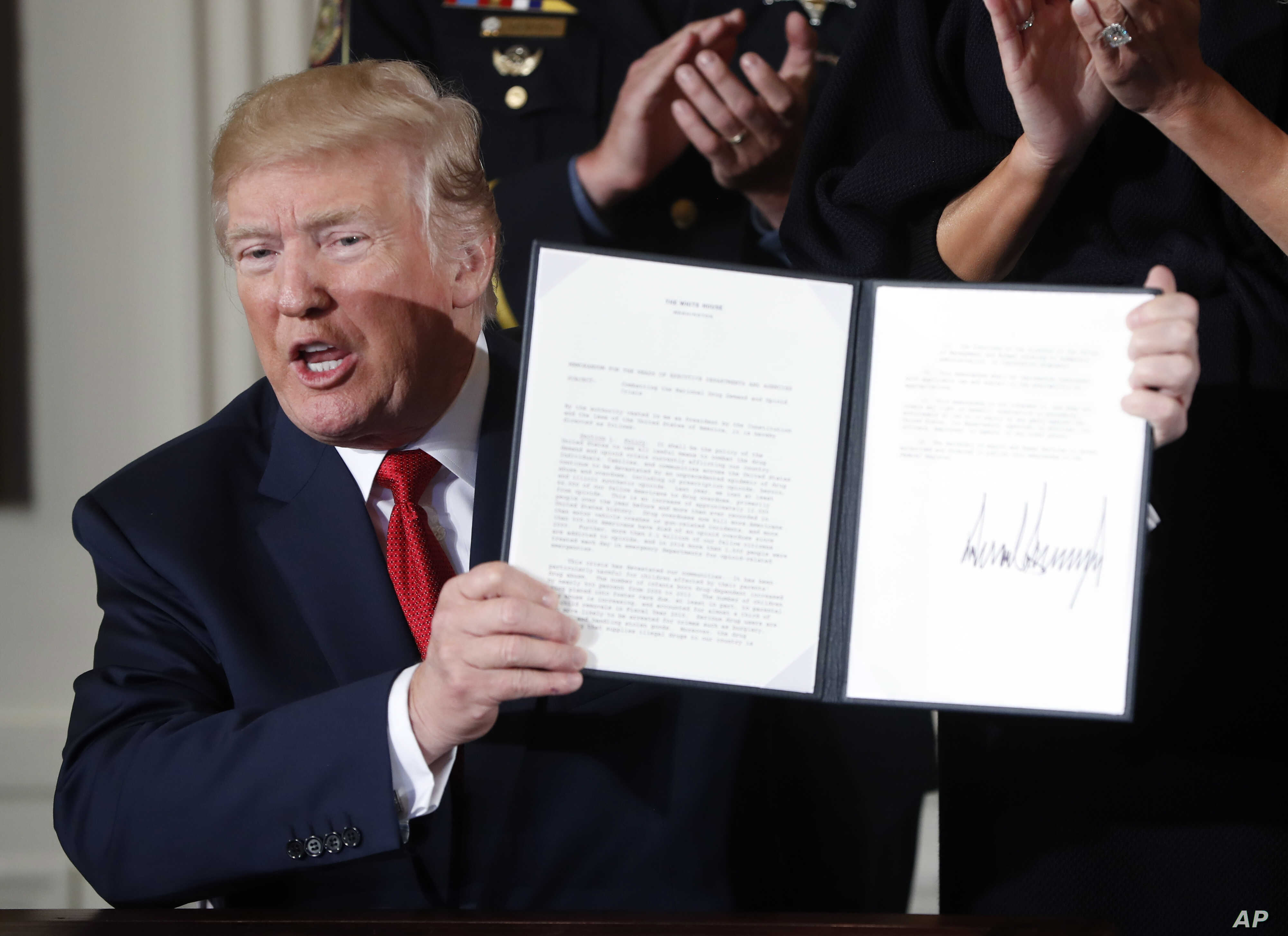 FILE - President Donald Trump displays a presidential memorandum he signed, declaring the opioid crisis a public health emergency, in the East Room of the White House, Oct. 26, 2017, in Washington.