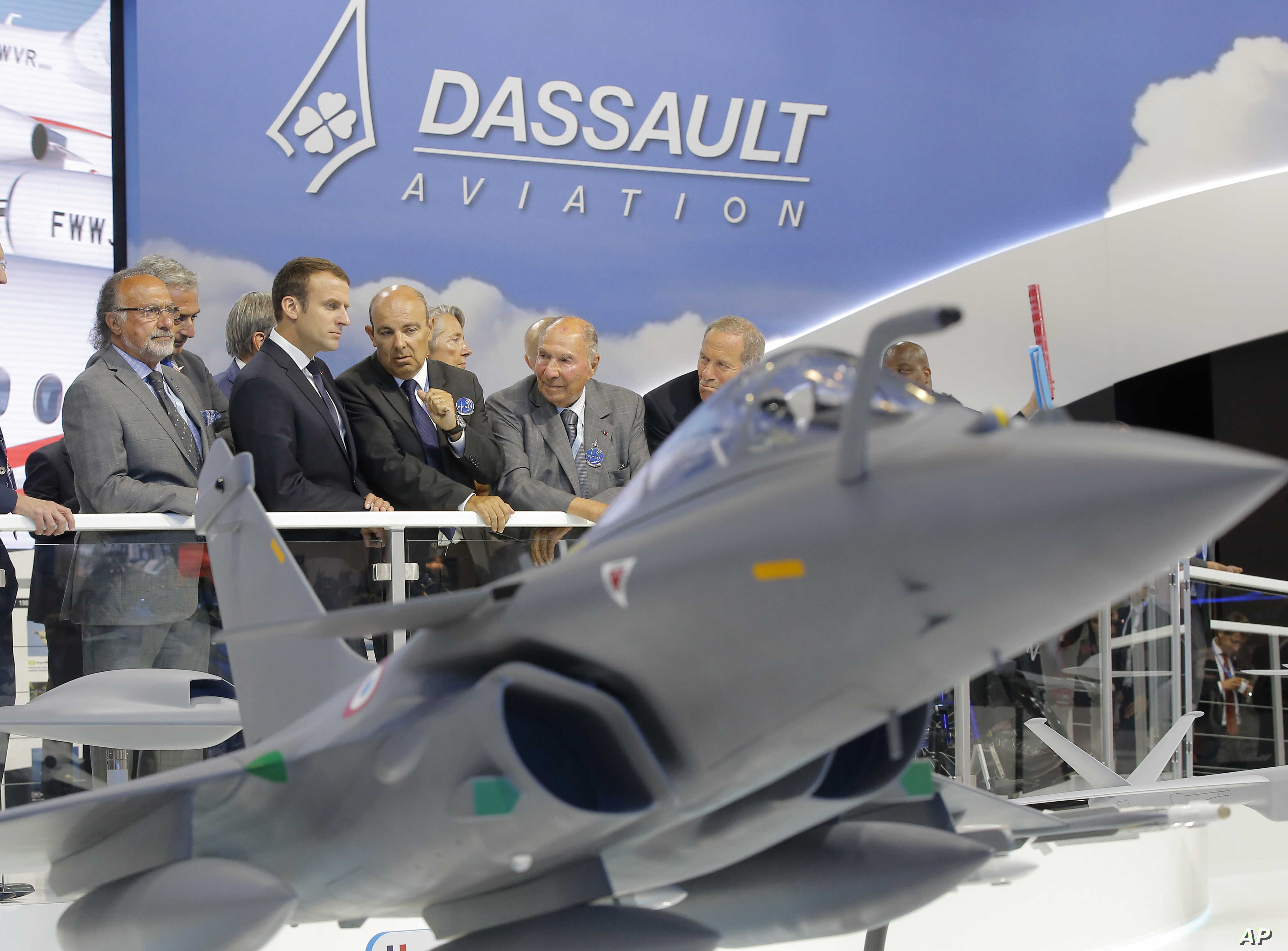 French President Emmanuel Macron, second left, listens to Dassault Aviation CEO Eric Trappier, center, while visiting the Paris Air Show in Le Bourget, June 19, 2017. Macron landed at the Bourget airfield in an Airbus A400-M military transport plane ...