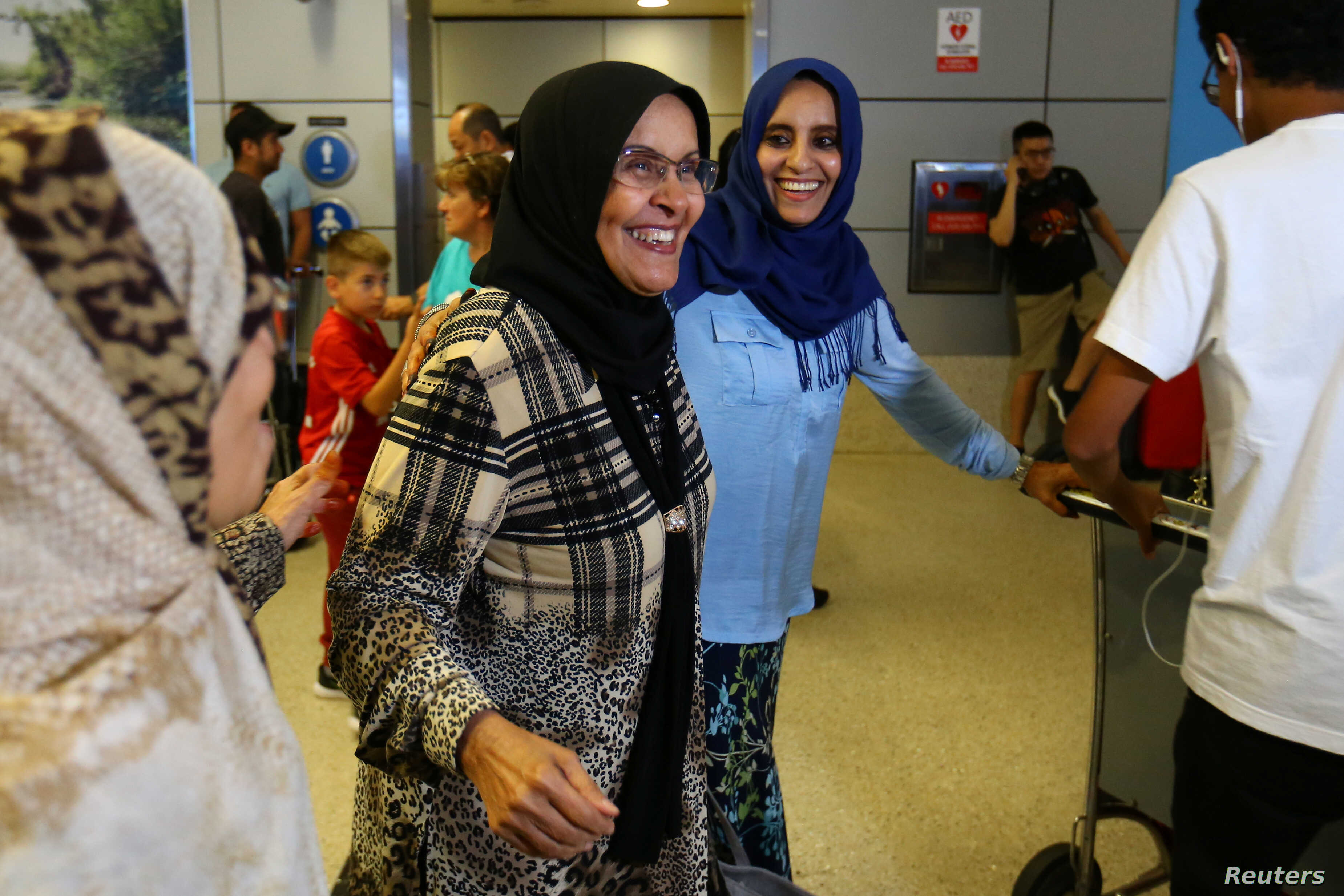 Hanadi Al-Hai, right, welcomes her mother traveling from Jordan on a Yemeni passport following the reinstatement by the U.S. Supreme Court of portions of President Donald Trump's executive order targeting travelers from six predominantly Muslim count...