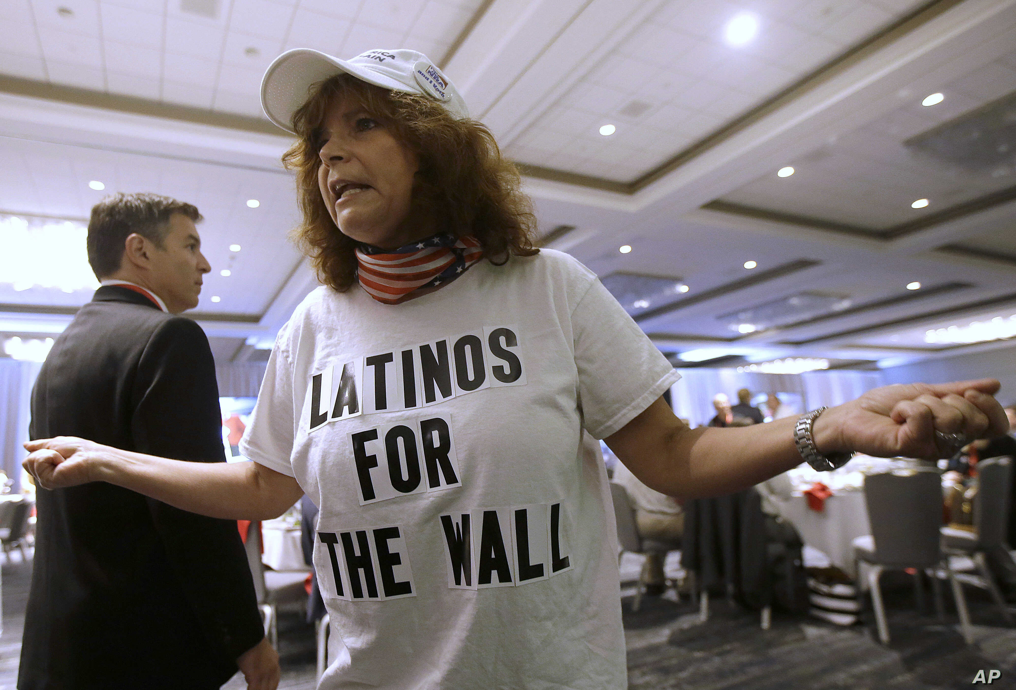 FILE - Republican presidential candidate Donald Trump supporter Luisa Aranda gestures as she is interviewed before Trump spoke at the California Republican Party 2016 Convention in Burlingame, Calif.