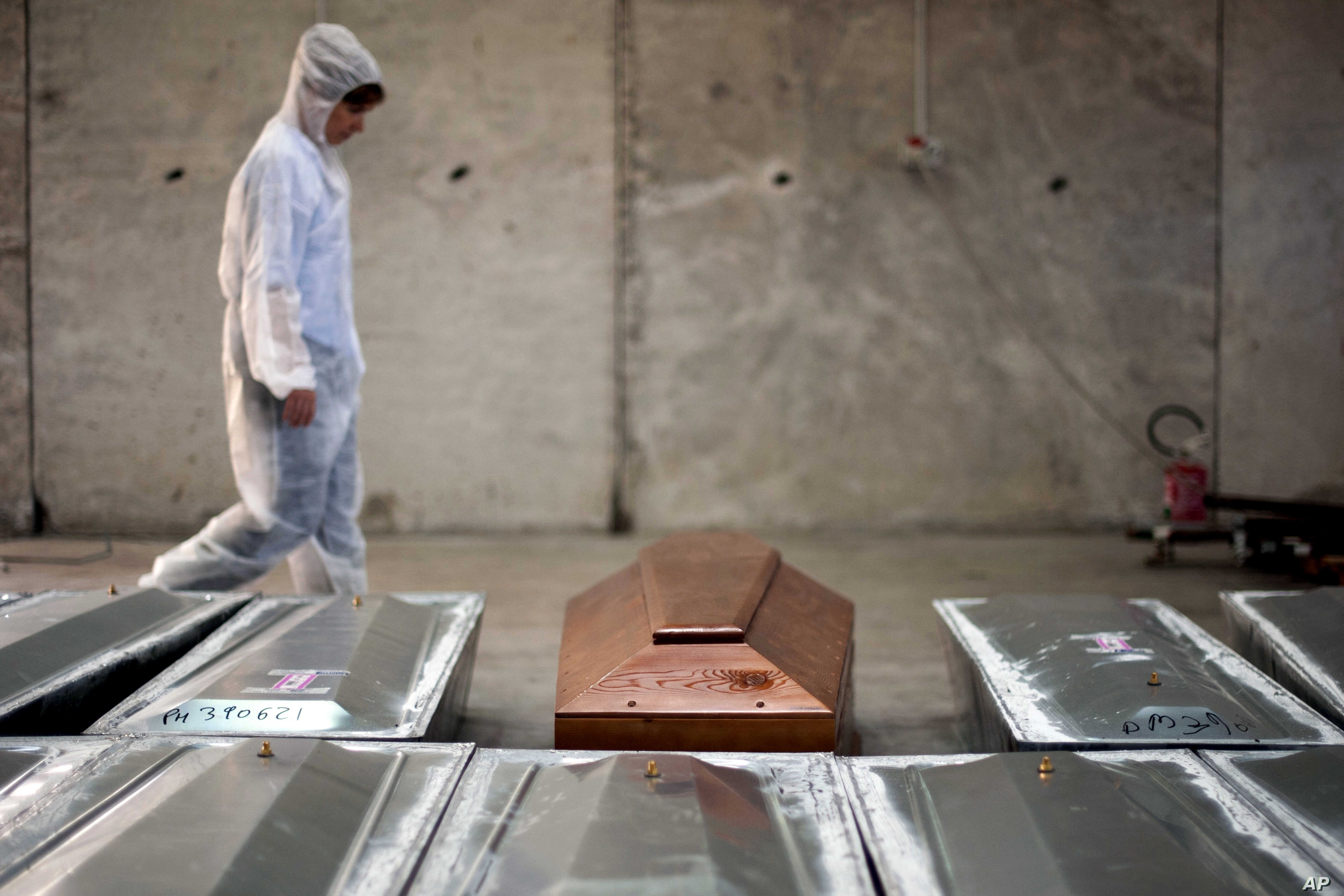 FILE - In this Oct. 8, 2016 file photo, a woman walks past rows of coffins at the NATO base in the Sicilian town of Melilli, Italy, where forensic investigator Cristina Cattaneo is one of two investigators trying to keep Italy's promise to trace the ...