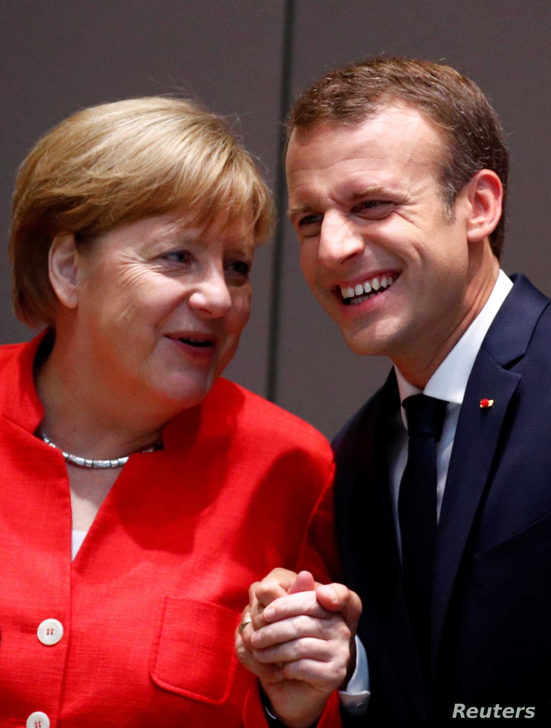 FILE - German Chancellor Angela Merkel shares a laugh with French President Emmanuel Macron as they arrive at a European Union leaders summit in Brussels, Belgium, June 29, 2018.
