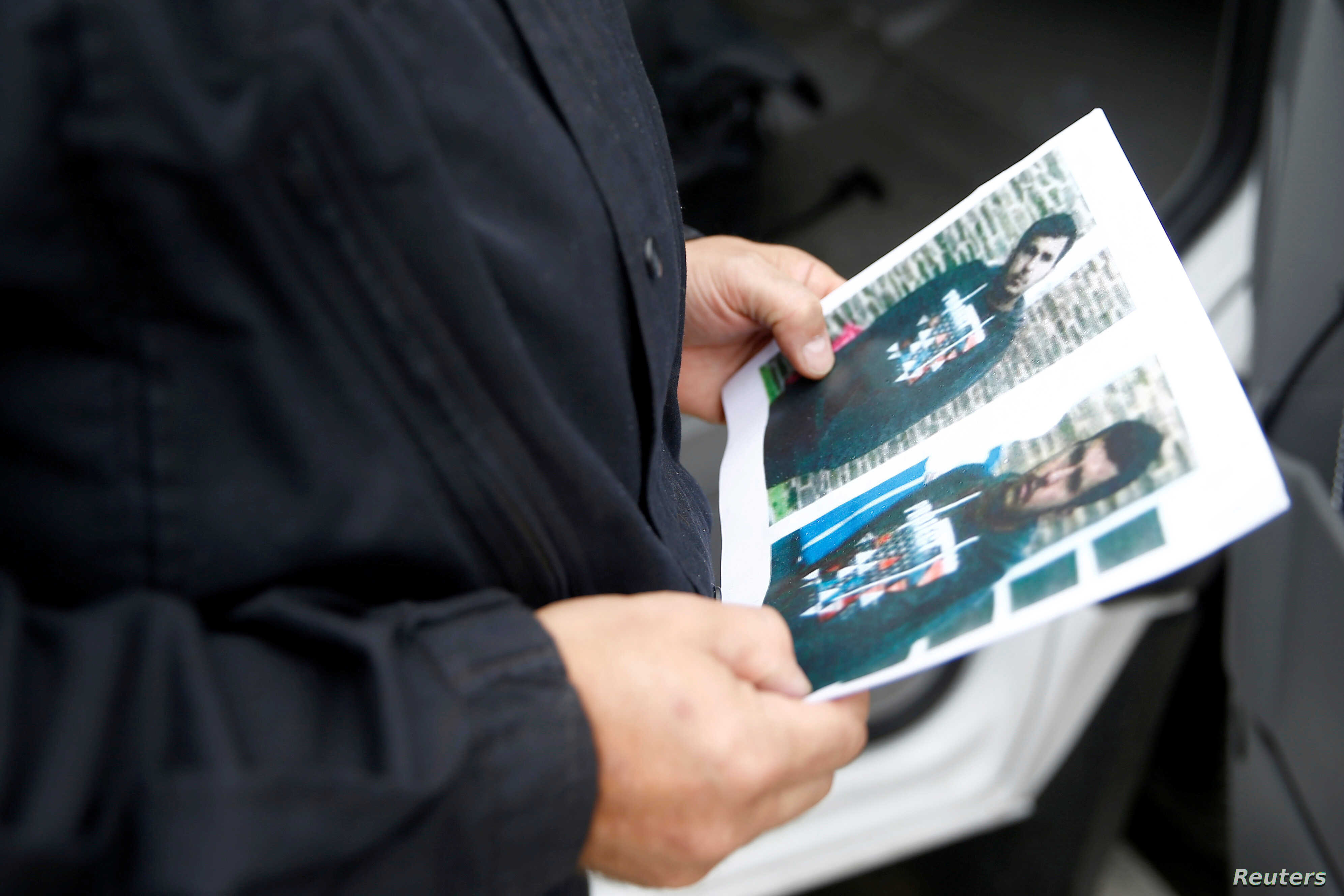 A German policeman holds the picture of a terrorist-subject infront of the main terminal of Berlin-Schoenefeld airport, in Schoenefeld, near Berlin, Oct. 9, 2016, following a suspicion that a bomb attack was being planned in Germany.