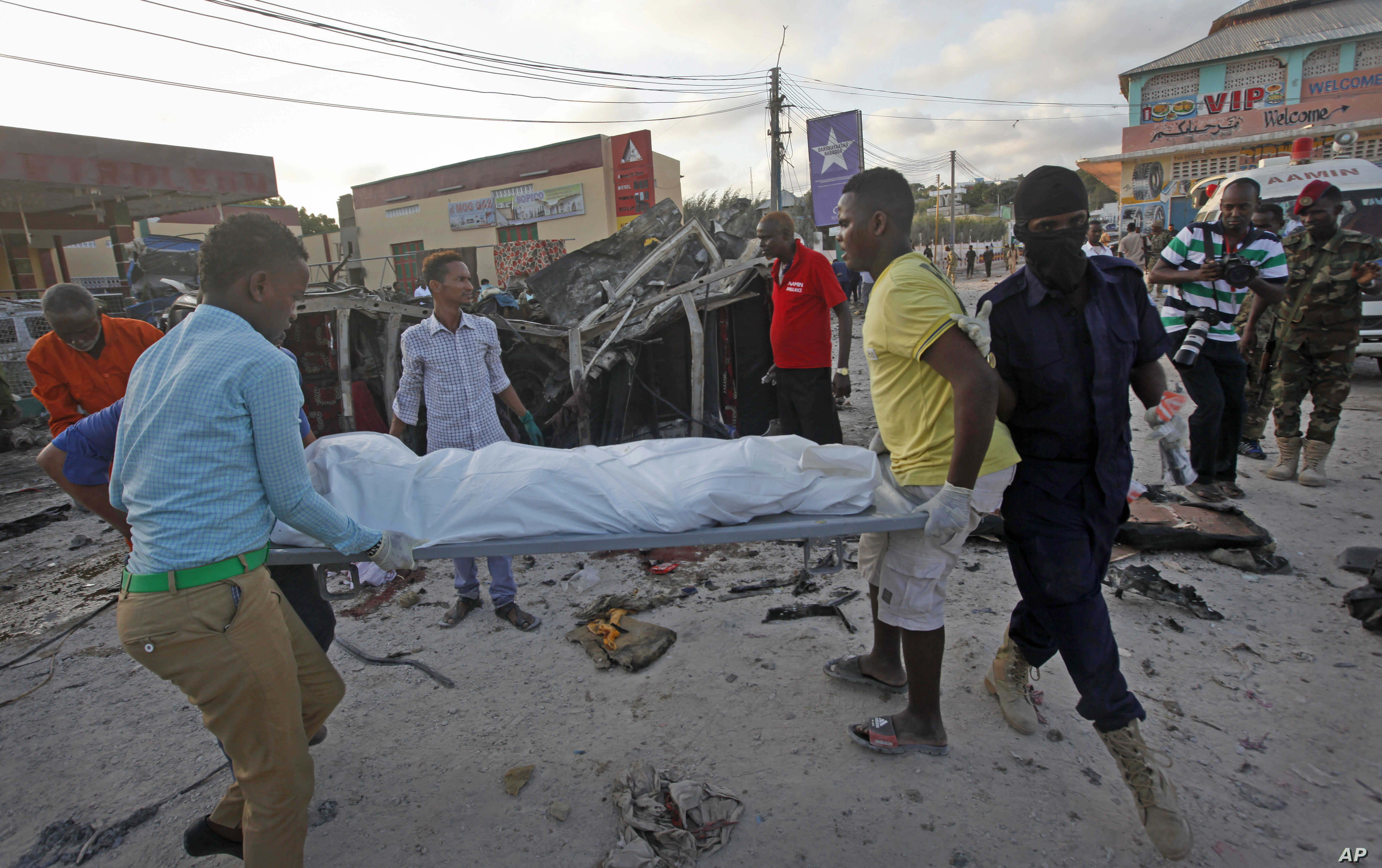 Somalis carry away the body of a civilian who was killed in a car bomb attack in Mogadishu, Somalia, Sept. 28, 2017. Police say the explosion outside a restaurant in Mogadishu's Hamarweyne district has killed at least seven people, mostly civilians.