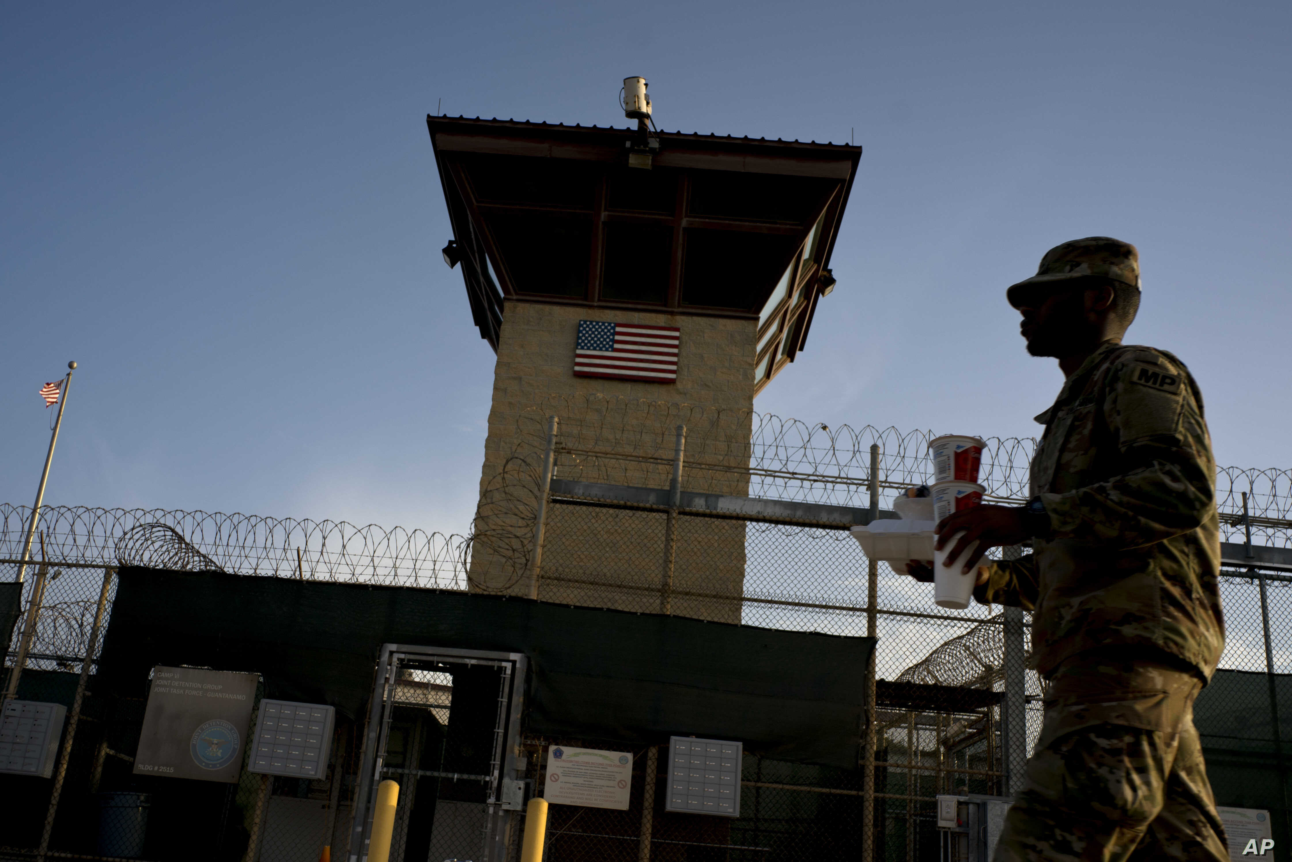 In this June 5, 2018 photo, reviewed by U.S. military officials, a task force member walks past the Camp 6 detention facility at the Guantanamo Bay U.S. Naval Base, Cuba.
