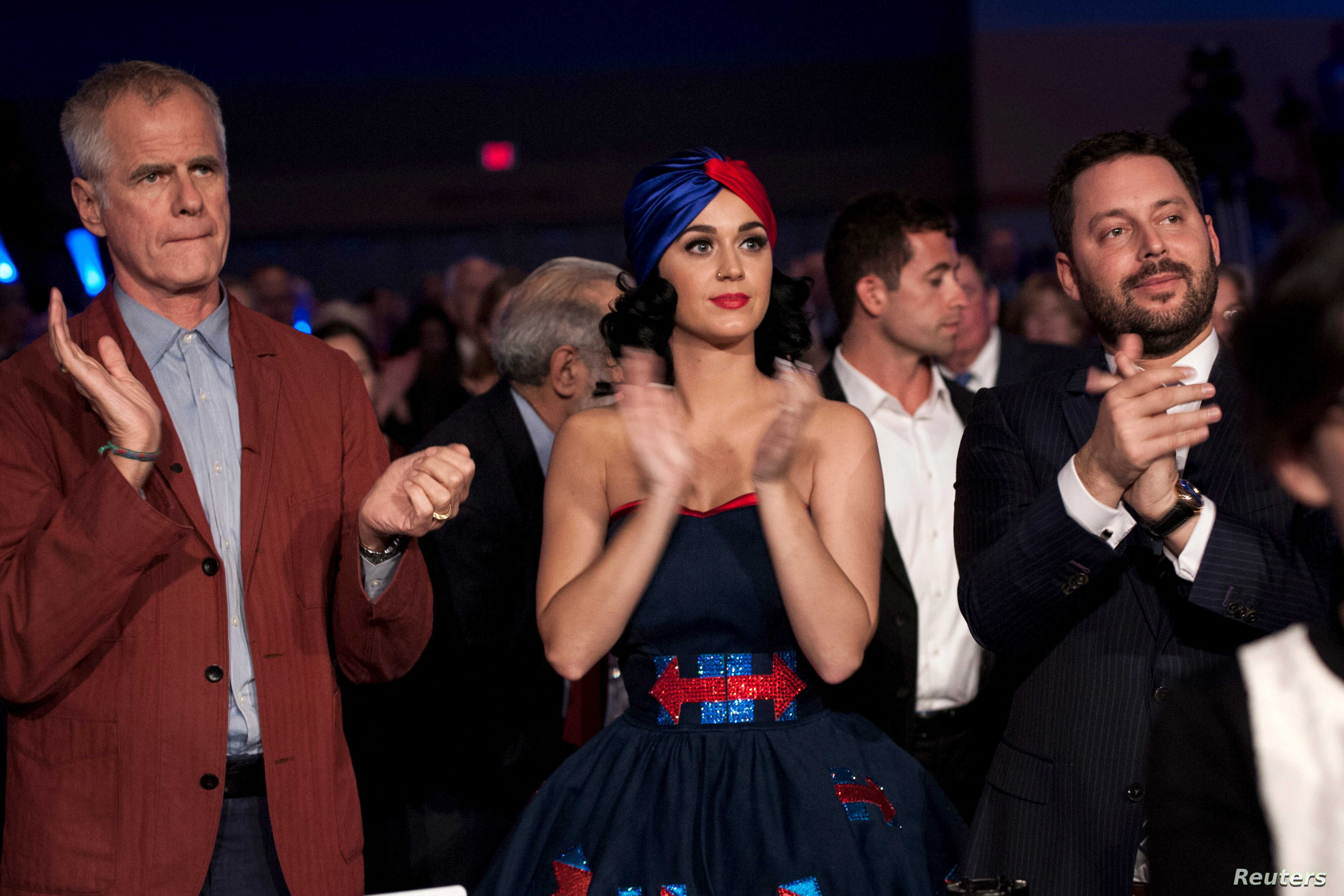 Singer Katy Perry, center, applauds as the Democratic candidates for president take the stage at the Jefferson-Jackson Dinner in Des Moines, Iowa, Oct. 24, 2015.