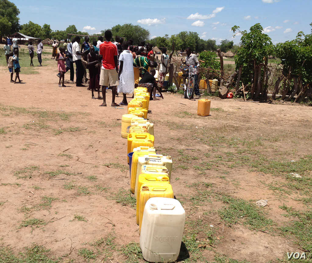 A long line of jerry cans waiting to be filled at the only borehole in a sector of Rhino refugee camp in Uganda that houses thousands of refugees.