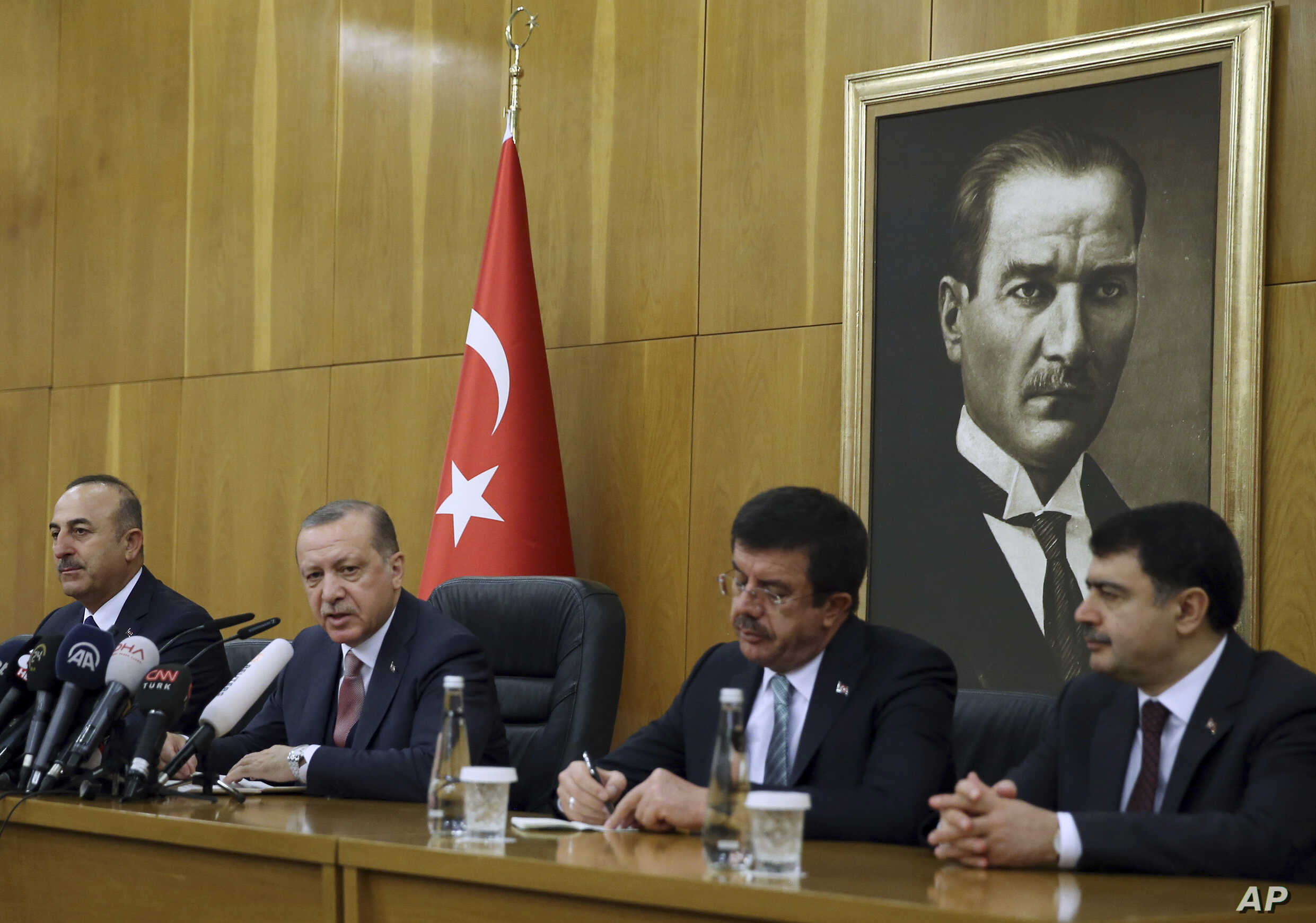 FILE - Turkish President Recep Tayyip Erdogan, second left, flanked by Foreign Minister Mevlut Cavusoglu, left, Economy Minister Nihat Zeybekci, second right, and Istanbul Gov. Vasip Sahin, speaks to reporters in Istanbul, Jan. 5, 2018. Erdogan slamm...