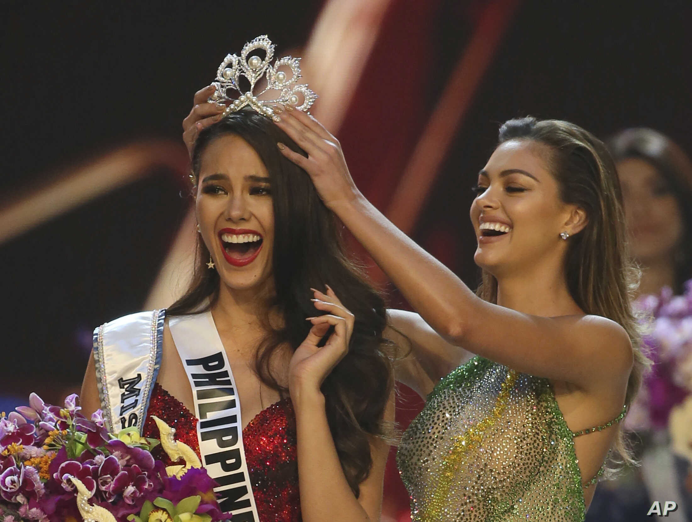 Catriona Gray of the Philippines, left, reacts as she is crowned the new Miss Universe 2018 by Miss Universe 2017 Demi-Leigh Nel-Peters during the Miss Universe competition in Bangkok, Thailand, Monday, Dec. 17, 2018.