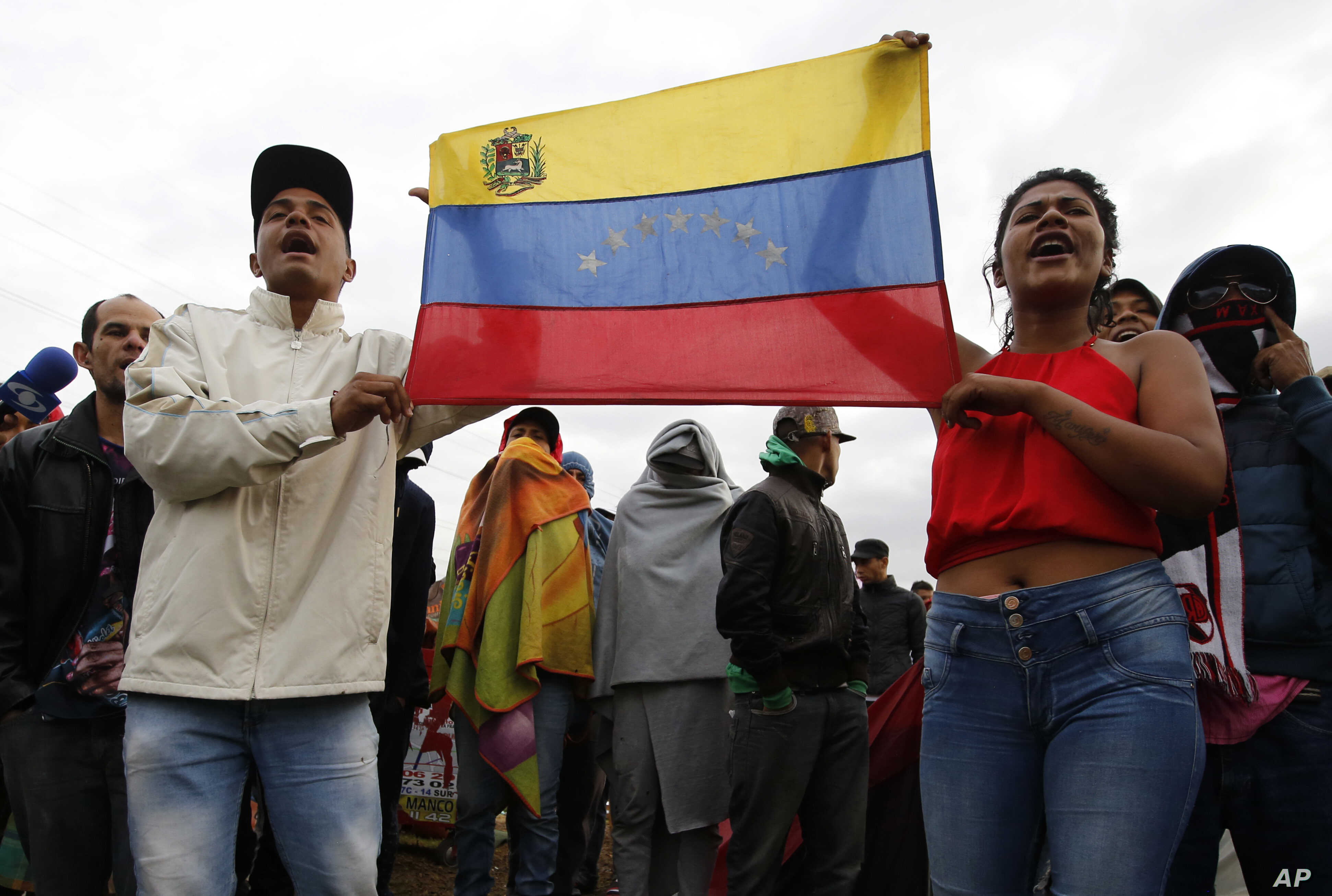 Venezuelan migrants protest the creation of a new, government-organized camp, which migrants can move to voluntarily, as they stand outside their current tent city near the main bus terminal in Bogota, Colombia, Nov. 13, 2018.