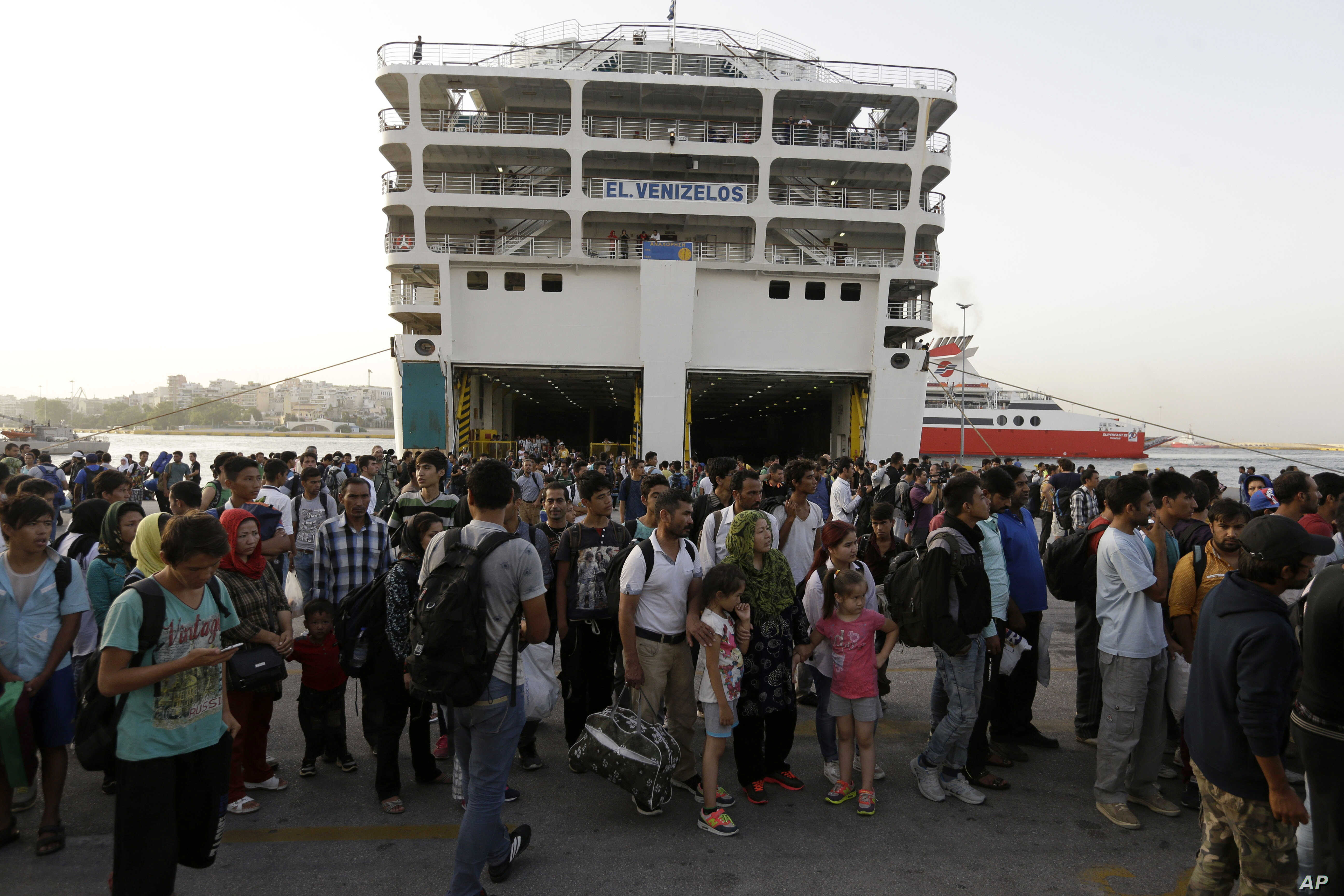 Refugees and migrants wait for a bus, transporting them to the metro station, after their arrival from the northeastern Greek island of Lesbos to the Athens' port of Piraeus, Sept. 7, 2015.