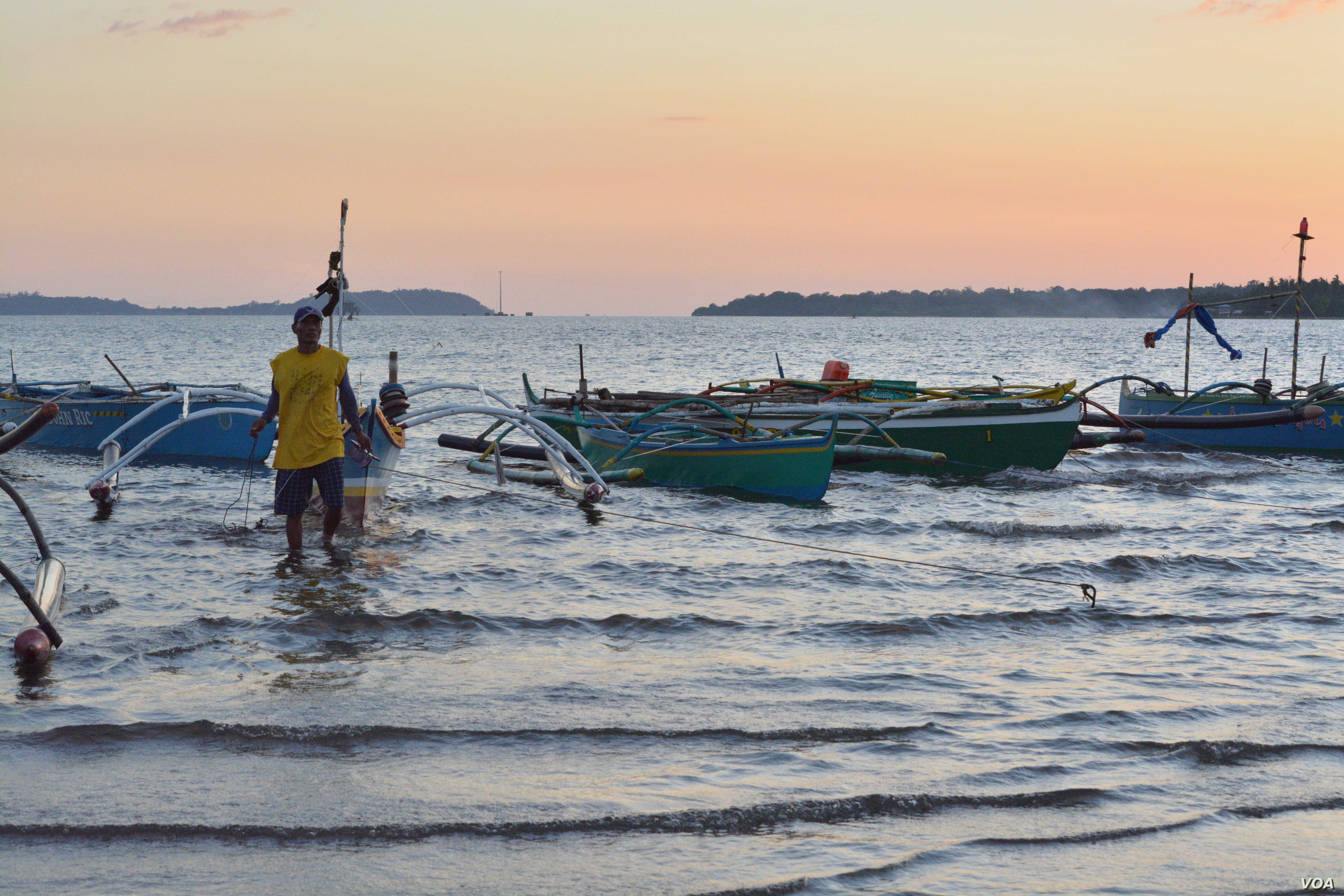 Fisherman Junick Josol starts removing the tow ropes of his tiny boat before heading out about 24 kilometers into the South China Sea to fish, Masinloc, Philippines, Nov. 8, 2015.  (S. Orendain/VOA)