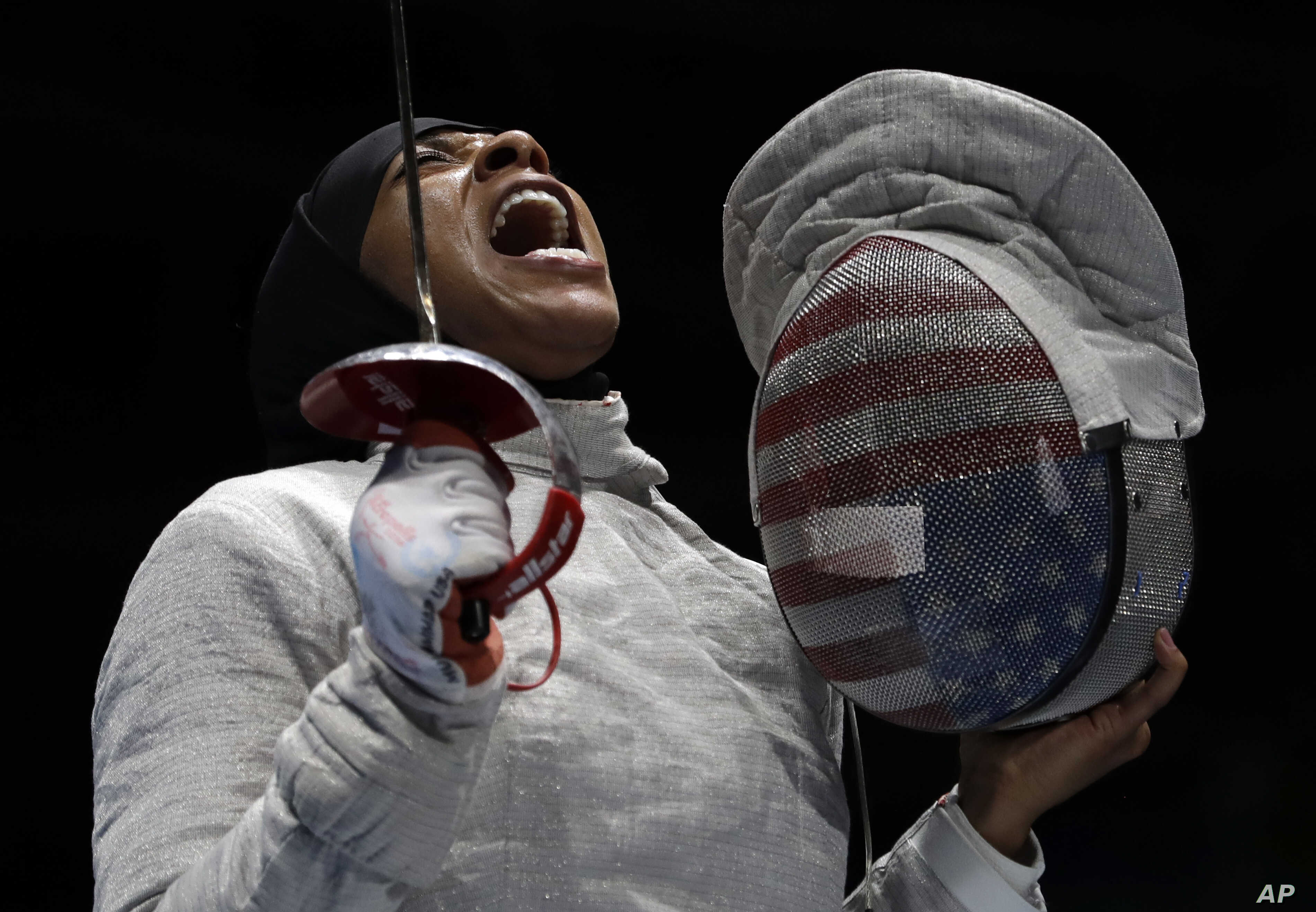 American Ibtihaj Muhammad celebrates after winning a point to Russia in a women's team sabre fencing semifinal at the 2016 Summer Olympics in Rio de Janeiro, Brazil, Aug. 13, 2016.