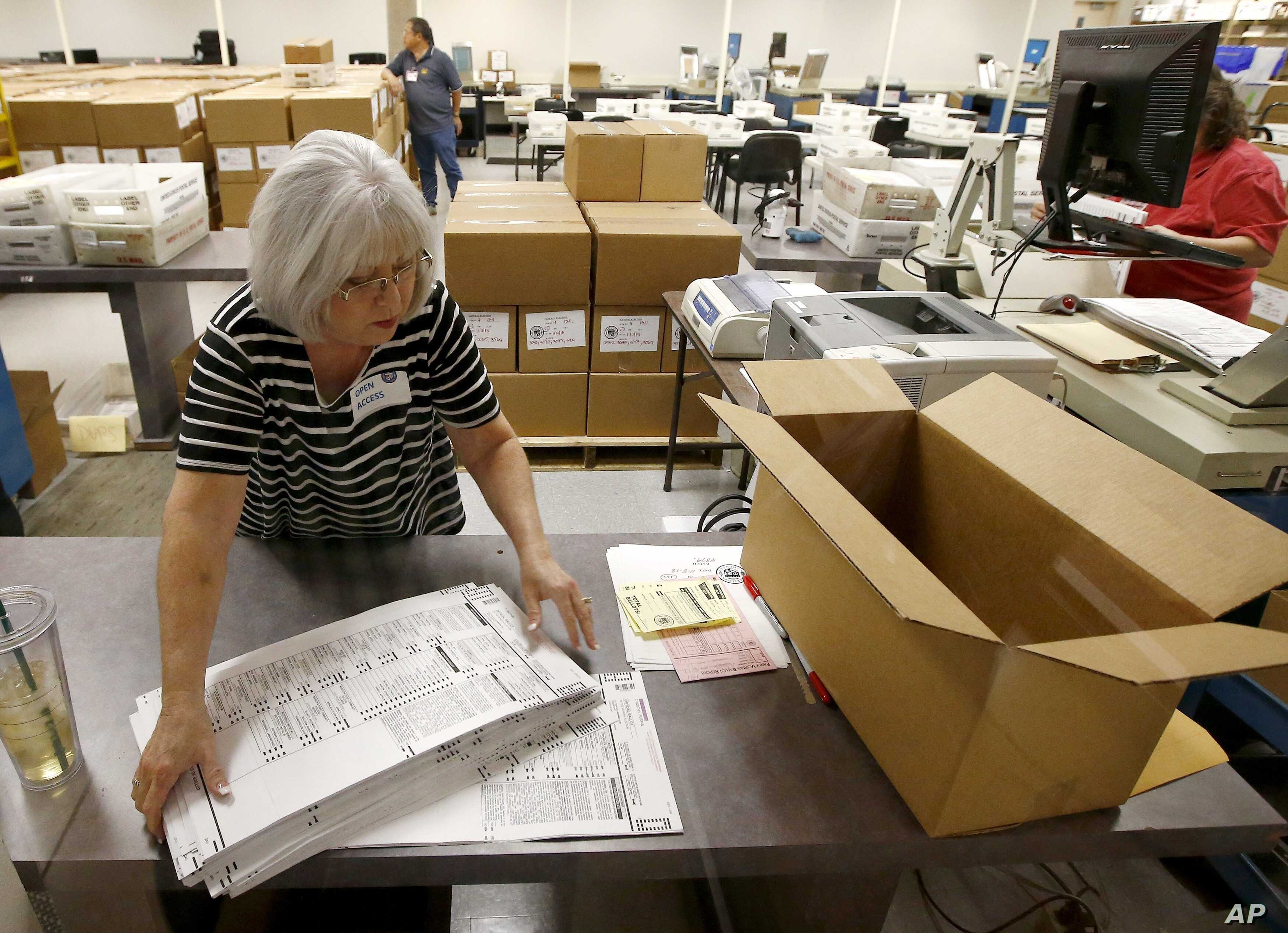 Workers at the Maricopa County recorder's office go through ballots  Nov. 8, 2018, in Phoenix. There are several races too close to call in Arizona, especially the Senate race between Democratic candidate Kyrsten Sinema and Republican candidate Marth...