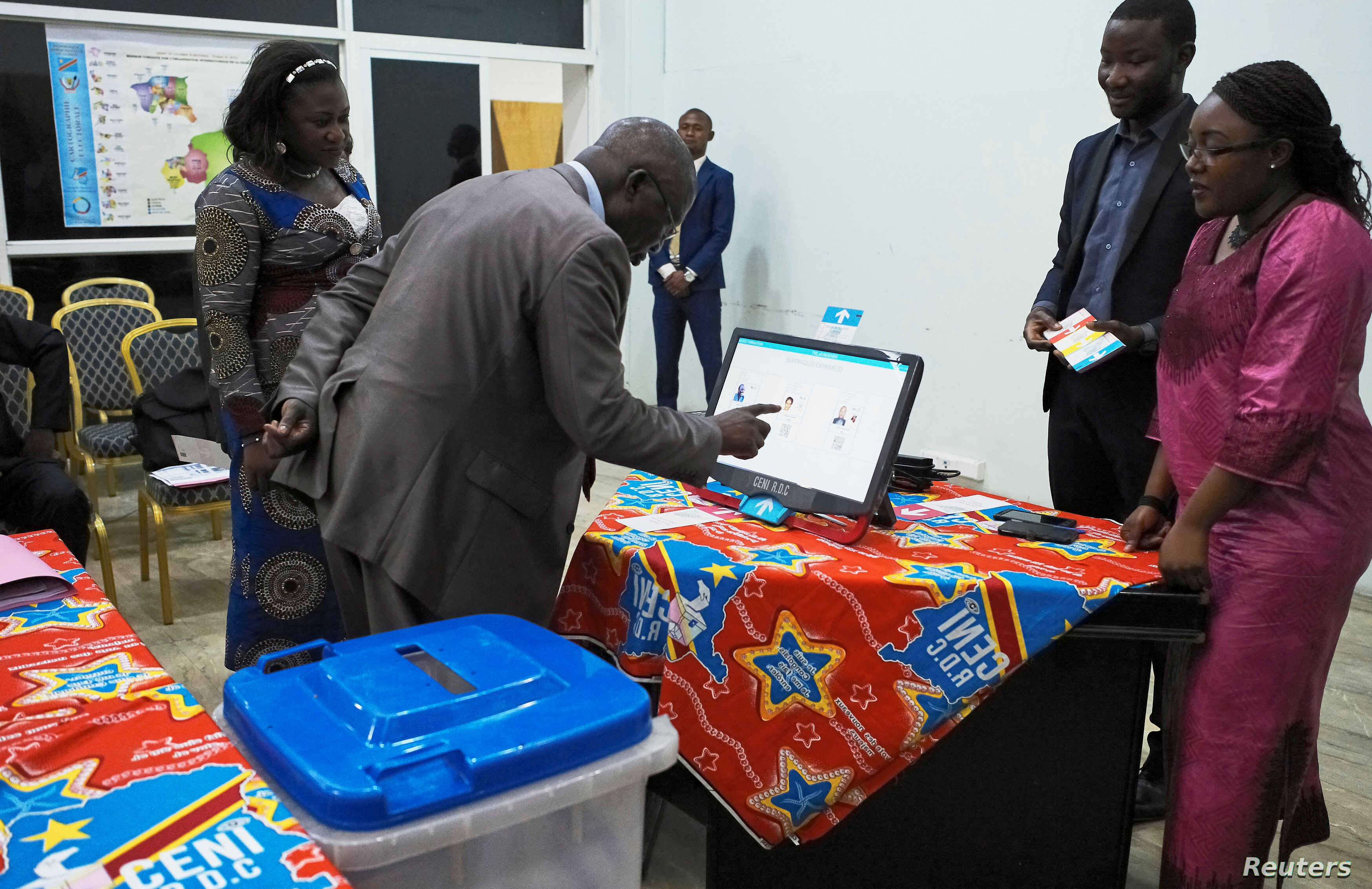 FILE - A man practices using an electronic voting machine during a demonstration inside Congo's electoral commission (CENI) head offices in Gombe Municipality of Kinshasa, Democratic Republic of Congo, March 1, 2018.