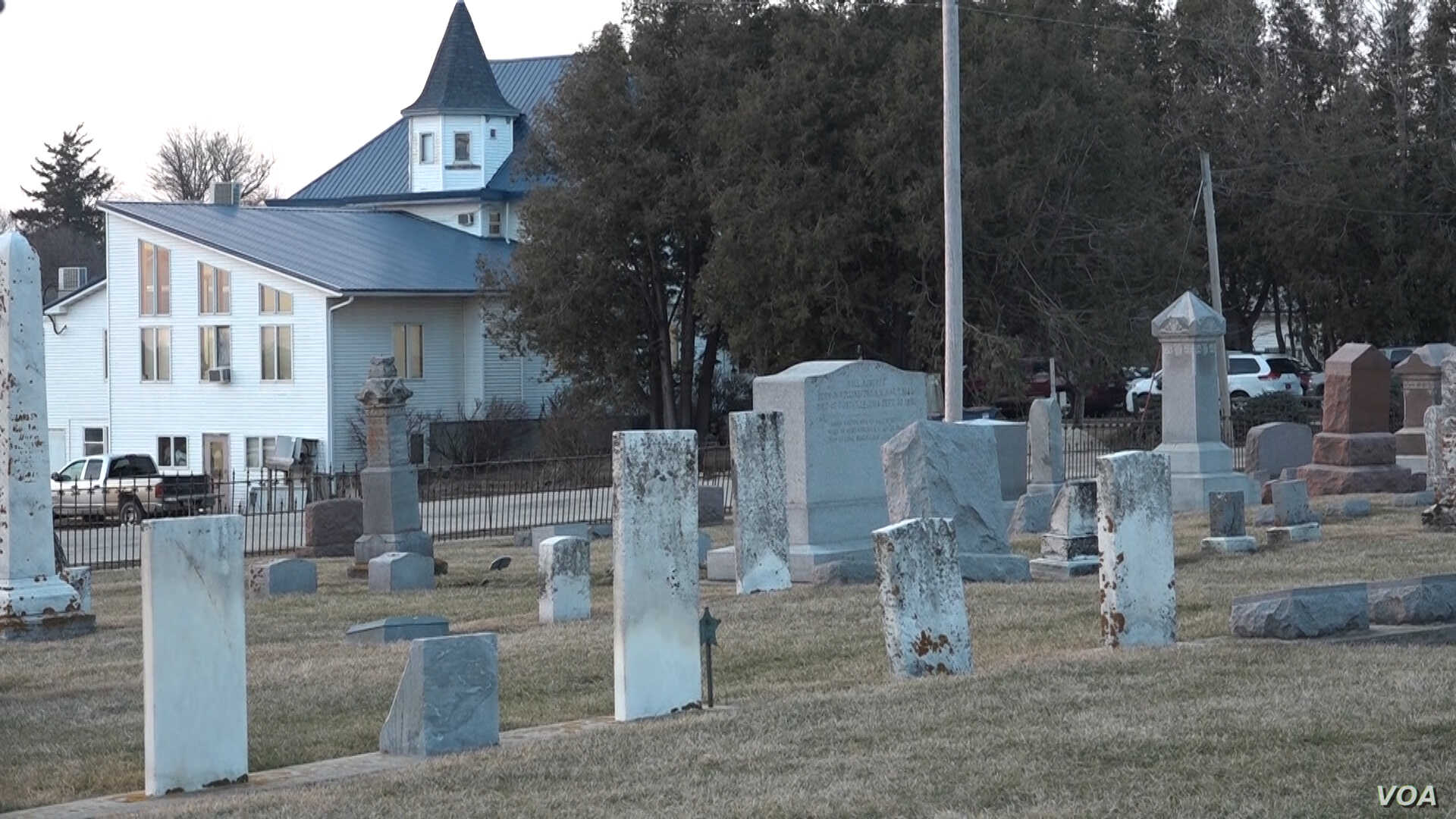 Behind these tombstones in a Christian cemetery is the house that serves as the synagogue for the Postville Jewish community. (G. Flakus/VOA)
