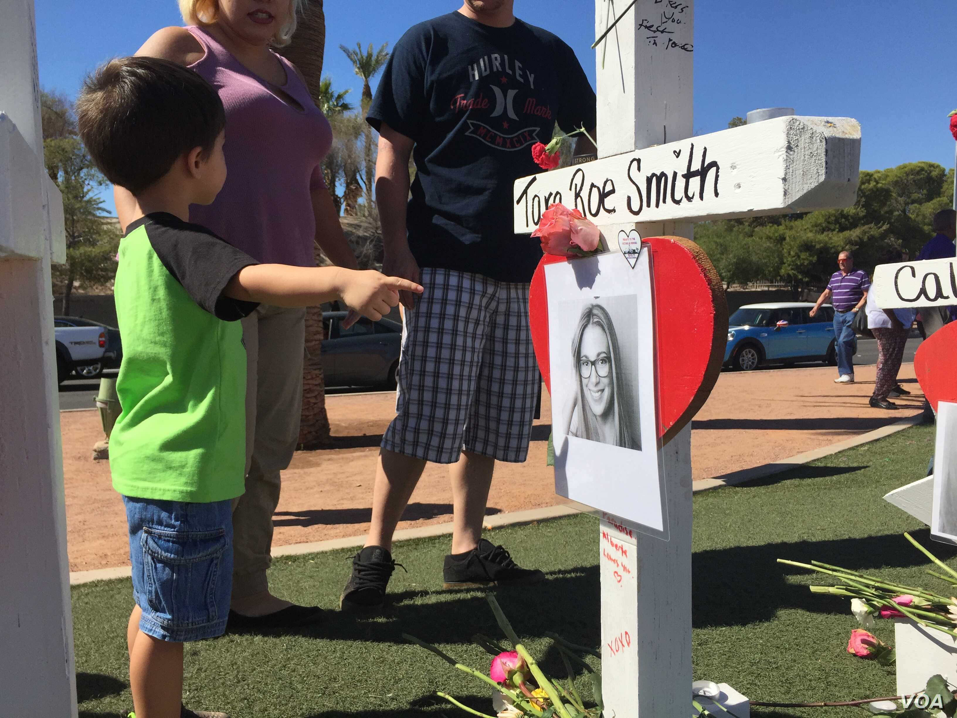 Parents brought their children to the memorial to see the crosses and honor the victims. The crosses honor the 59 people who died when a gunman opened fire on a country music concert, Oct. 1, 2017, in Las Vegas.