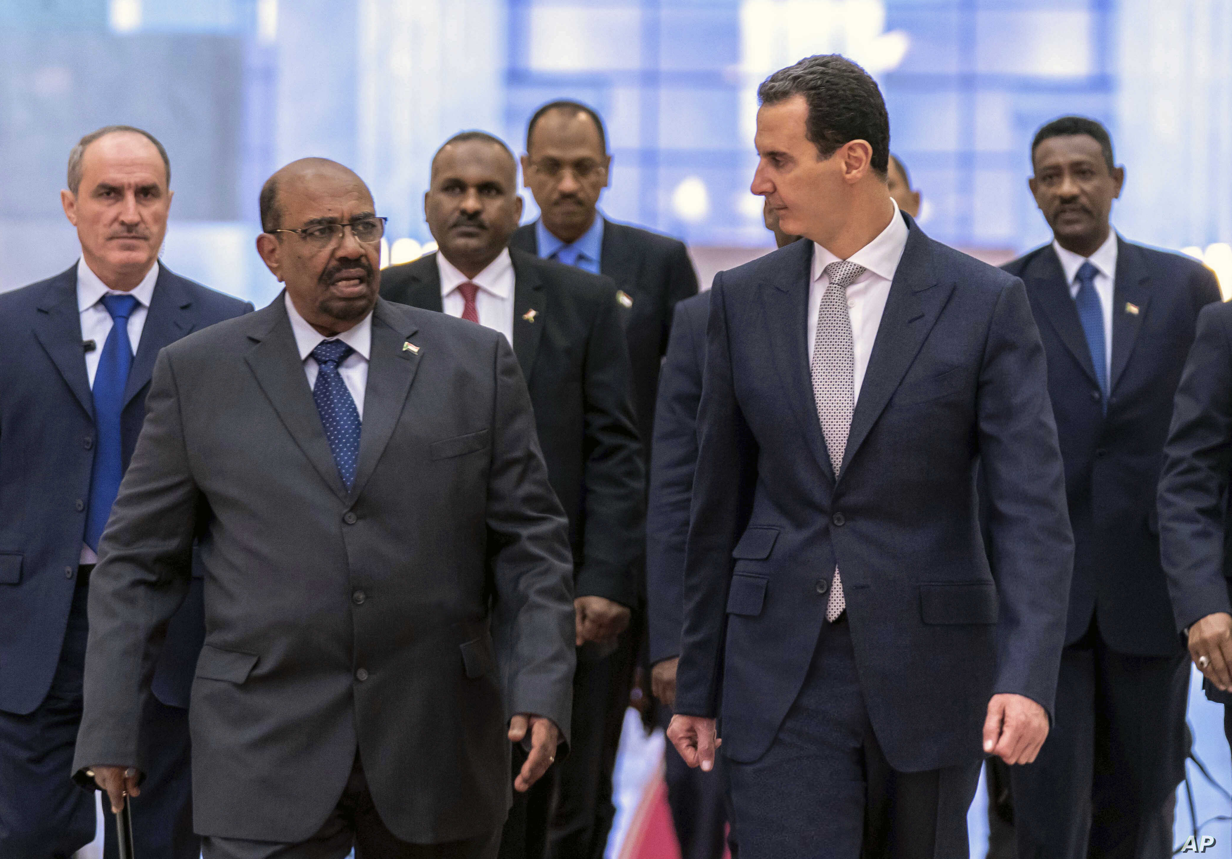 FILE - In this photo released by the Syrian official news agency SANA, Dec. 16, 2018, Syrian President Bashar Assad, right, meets with Sudan's President Omar Bashir in Damascus, Syria.