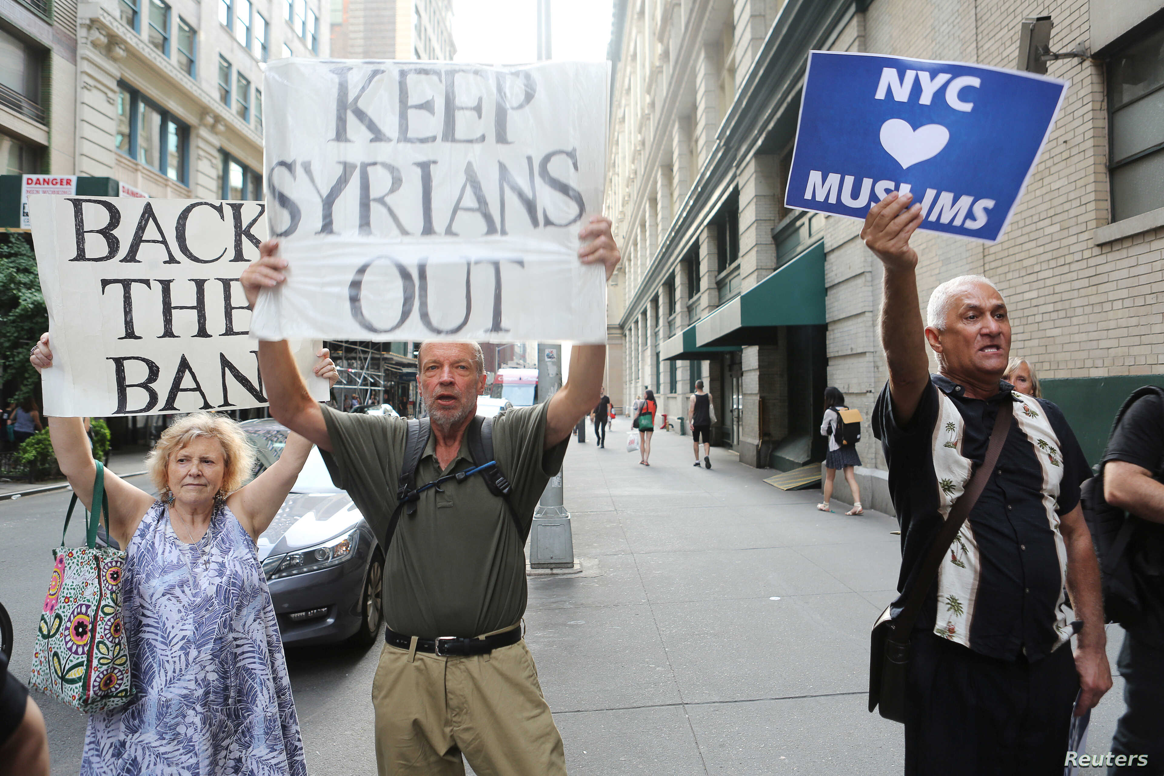 """A man holds a sign reading """"NYC hearts Muslims"""" as two other people hold signs reading """"Back the Ban"""" and """"Keep Syrians Out"""" at protests in response to U.S. President Donald Trump's limited travel ban, approved by the U.S. Supreme Court, in New York ..."""