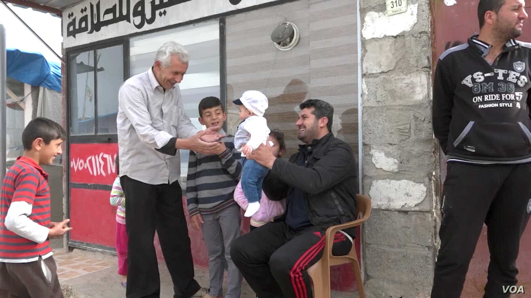 Hussain Ali smiles as he plays with an infant outside his small shop in Domiz, Iraq (VOA).