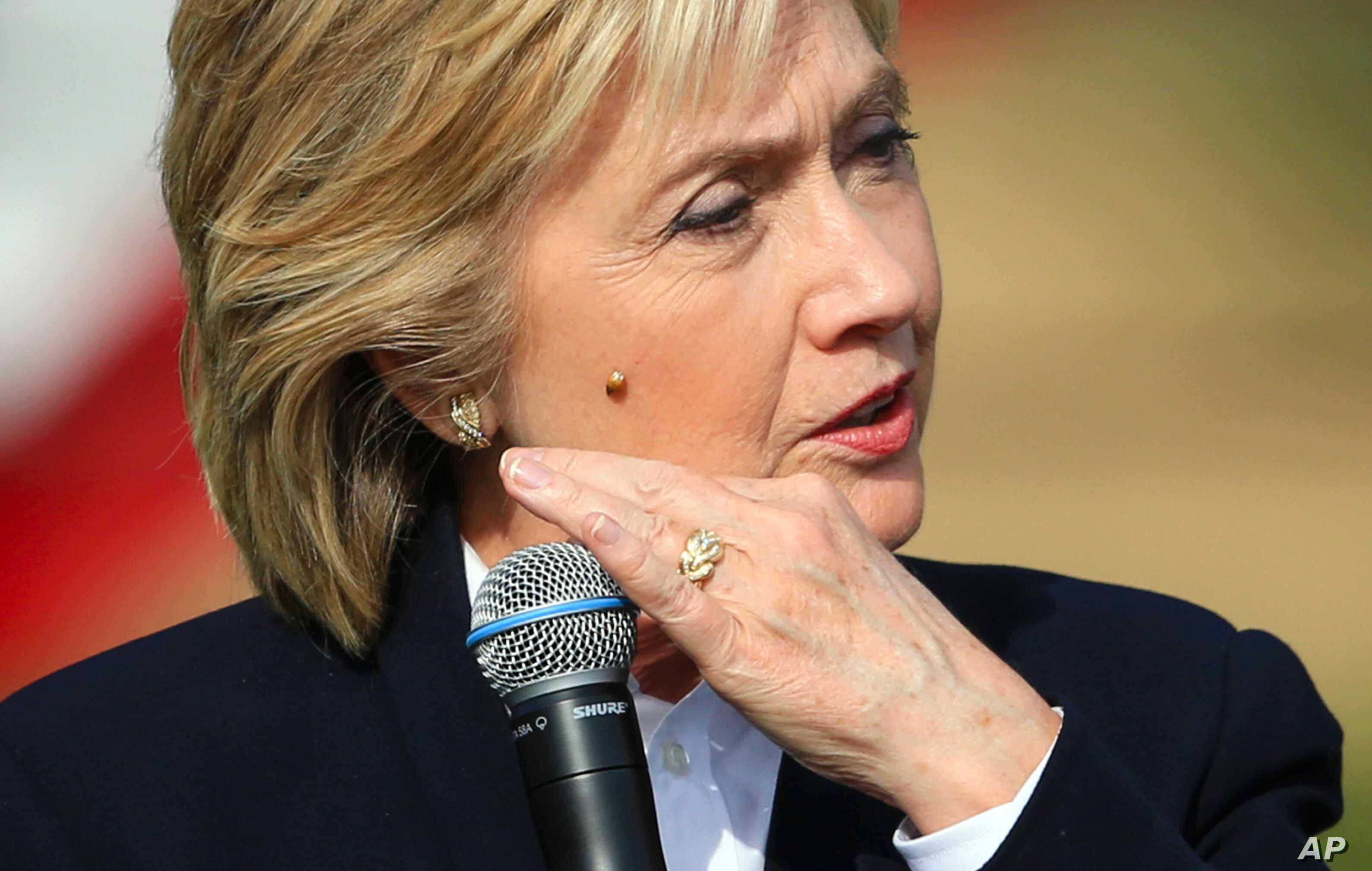 Democratic presidential candidate Hillary Rodham Clinton brushes off a lady bug that landed on her as she speaks Wednesday, Oct. 7, 2015, during a campaign stop at the Westfair Amphitheater in Council Bluffs, Iowa.