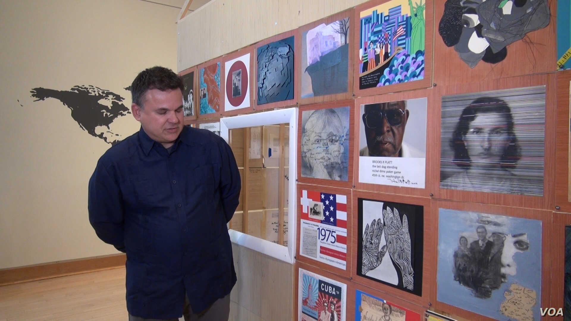 Artist Ric Garcia stands in front of a wall of panels, each one representing the immigrant background of a different artist. Garcia's is the panel from Cuba. (Jsoh/VOA)