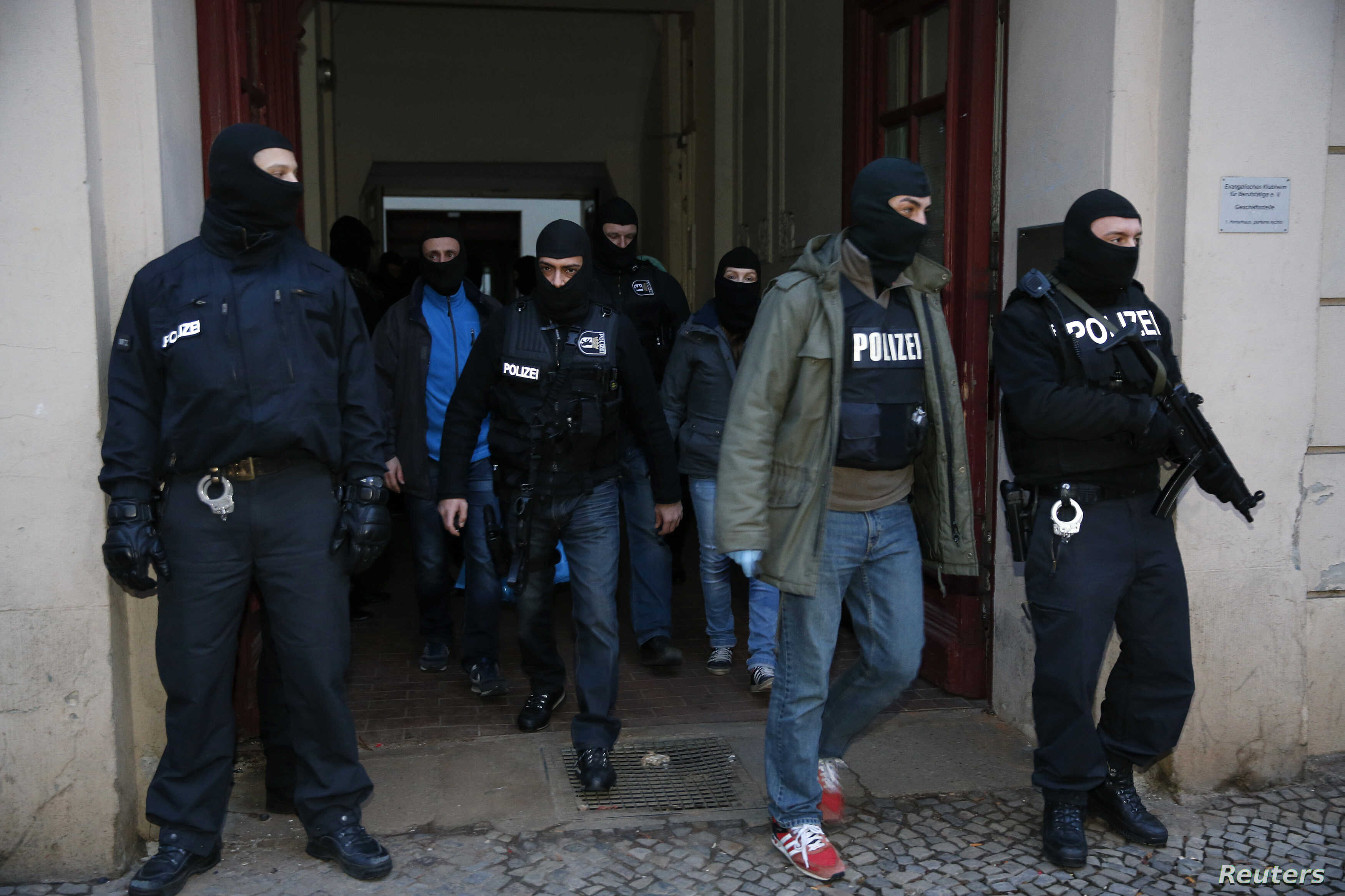 German special police units leave an apartment building in the Wedding district in Berlin January 16, 2015. Around 250 policemen took part in the raid and arrested two suspected Islamists, police said. REUTERS/Fabrizio Bensch (GERMANY - Tags: CIVIL U...
