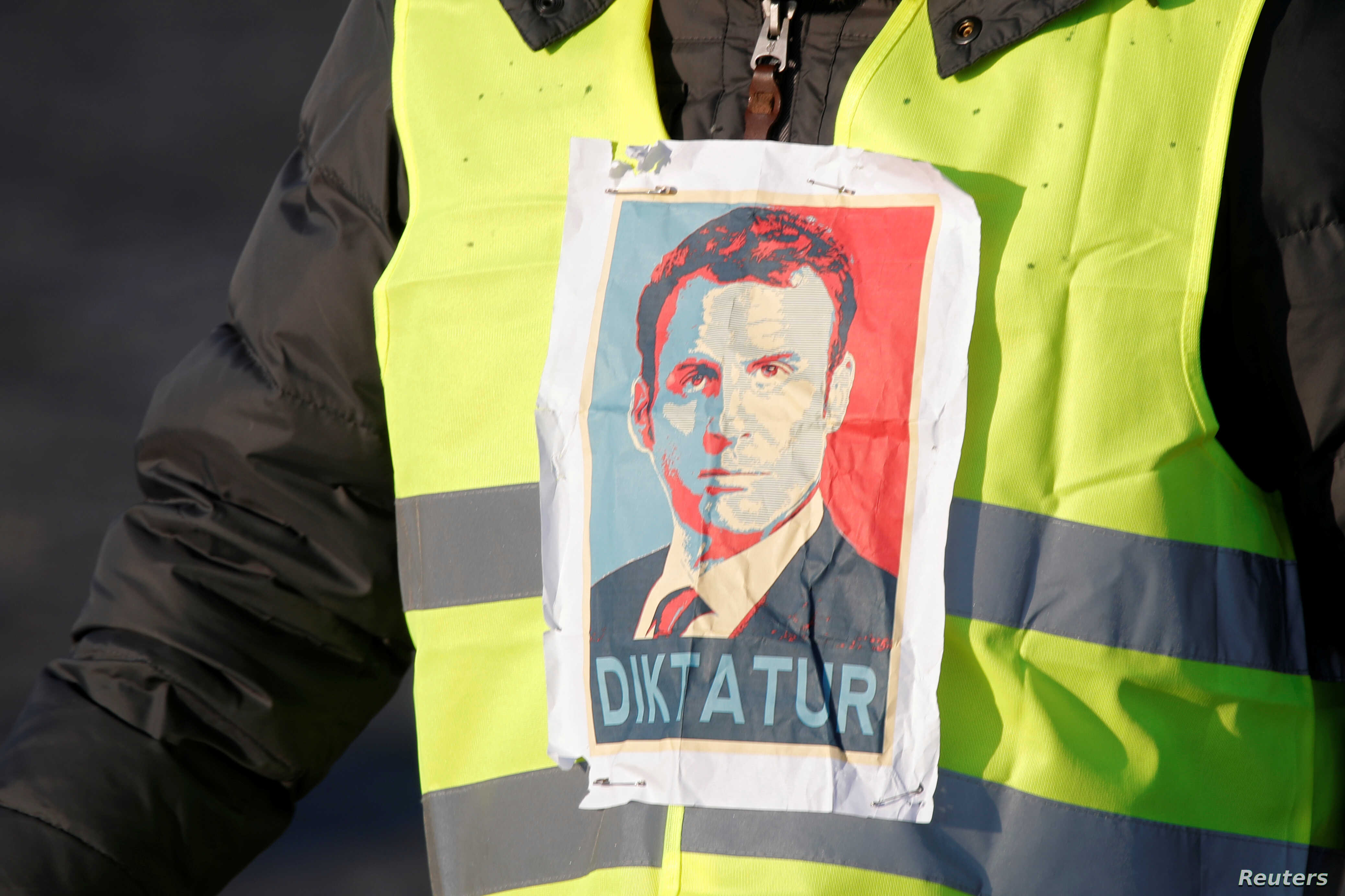 """A """"Yellow Vest"""" protester sports an image of French President Emmanuel Macron, with """"Diktatur,"""" the German word for """"Dictatorship,"""" written on it, in Paris, France, Nov. 17, 2018."""