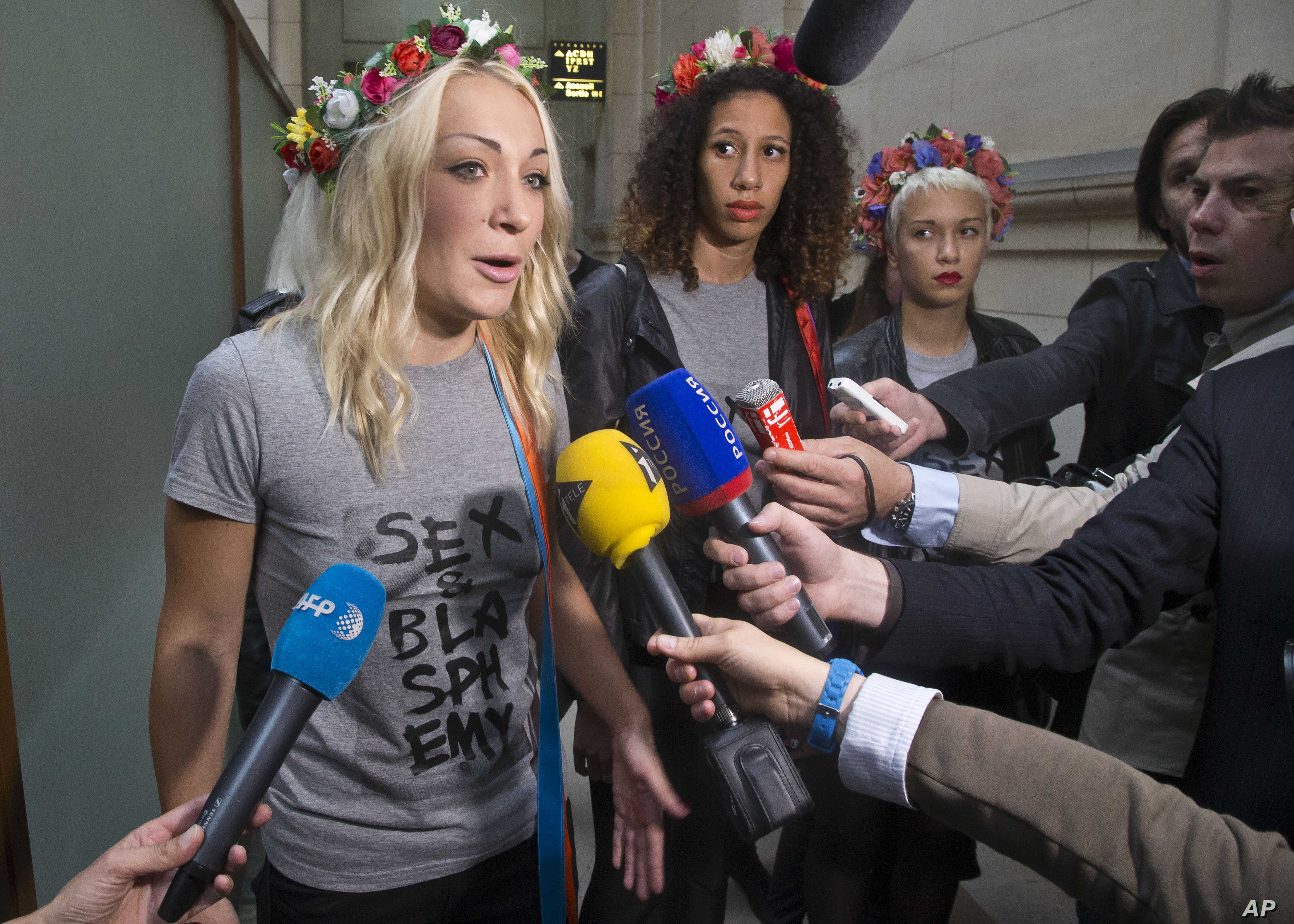 FILE - Leader of the feminist protest group Femen Ukrainian Inna Shevchenko, left, speaks to the media as she and other members of the group arrive at courhouse in Paris, July 9, 2014.