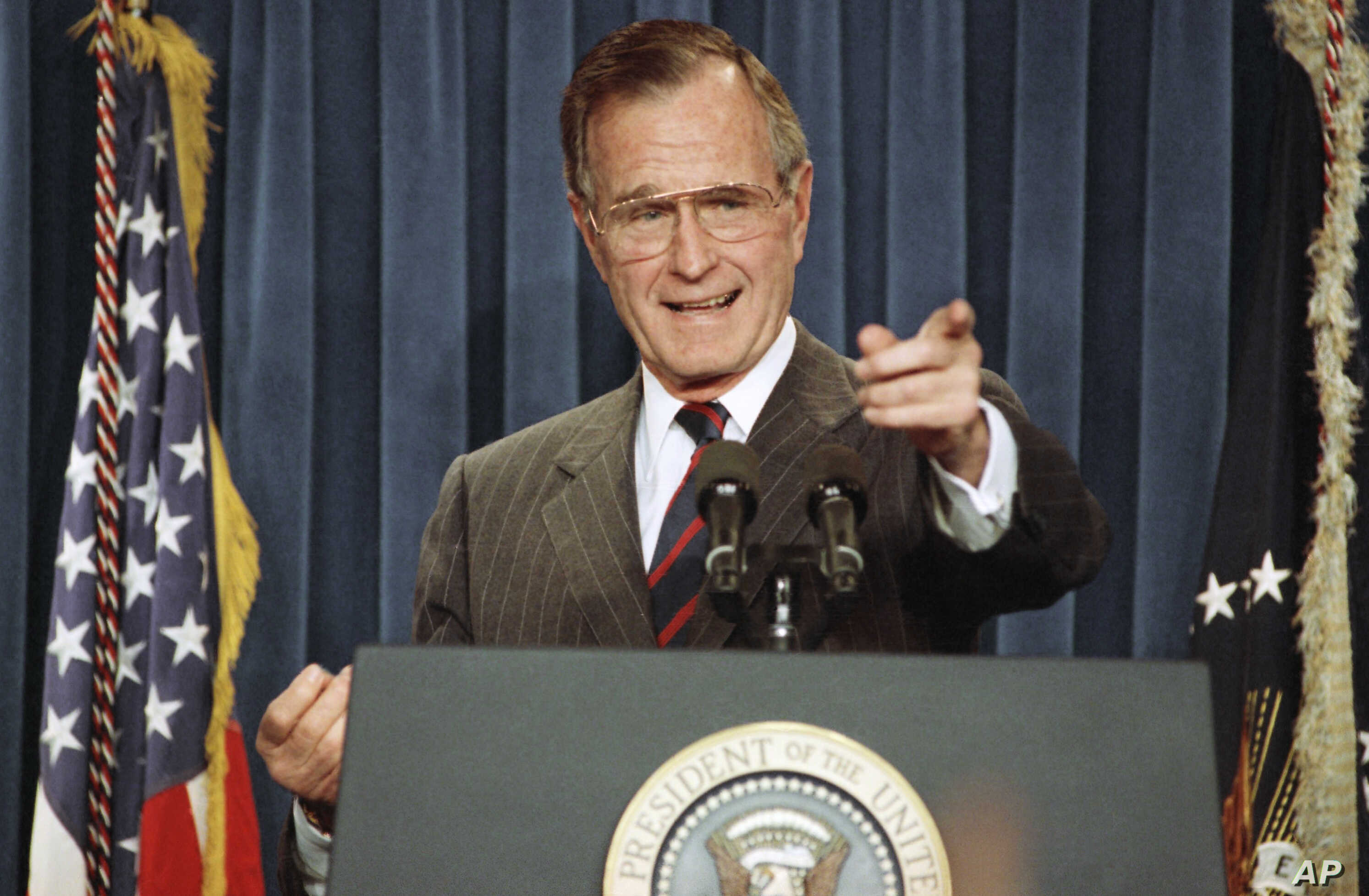 FILE - President George H.W. Bush acknowledges a reporter during a news conference at the White House, Dec. 5, 1991.
