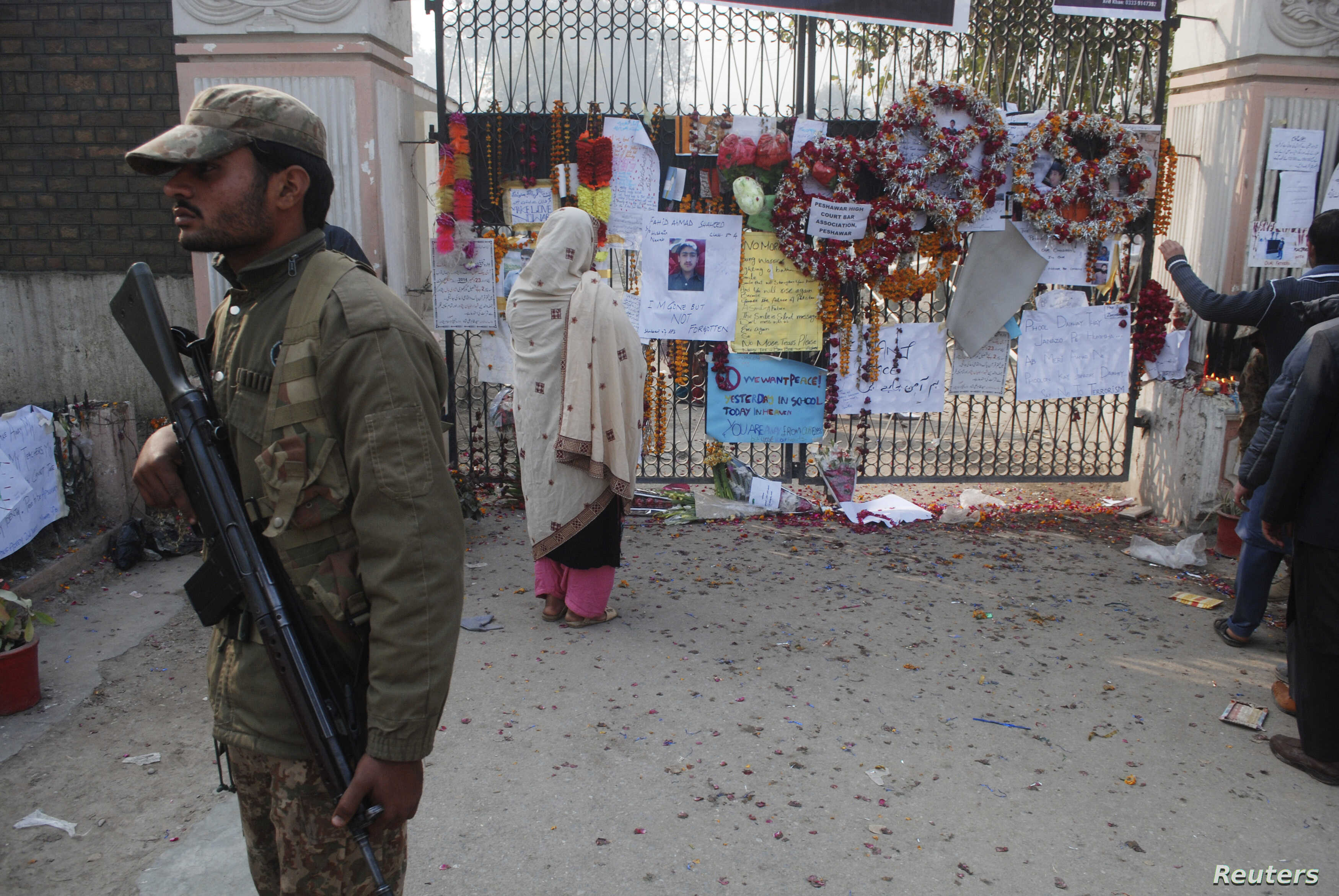 A soldier stands near a woman reading messages left by people for the victims of the Taliban attack on a school, in Peshawar, Pakistan, Dec. 23, 2014.