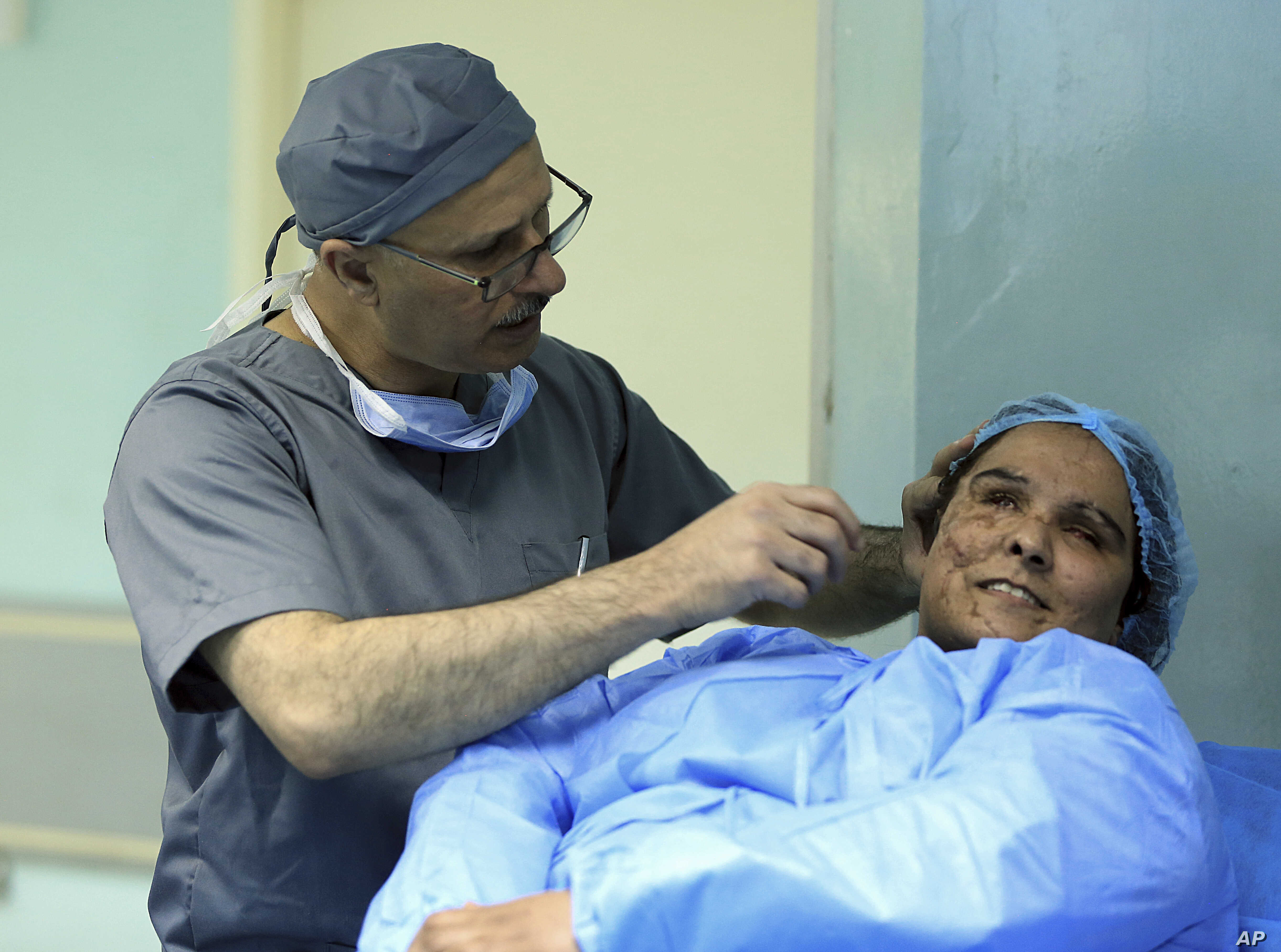 Plastic surgeon Dr. Abbas al-Sahan makes surgical marks around the damaged ear of Saja Ahmed Saleem, before her reconstructive surgery in Baghdad, Iraq, Nov. 6, 2018. Saleem lost both eyes, right arm and ear and suffered disfigurement in a bomb explo...
