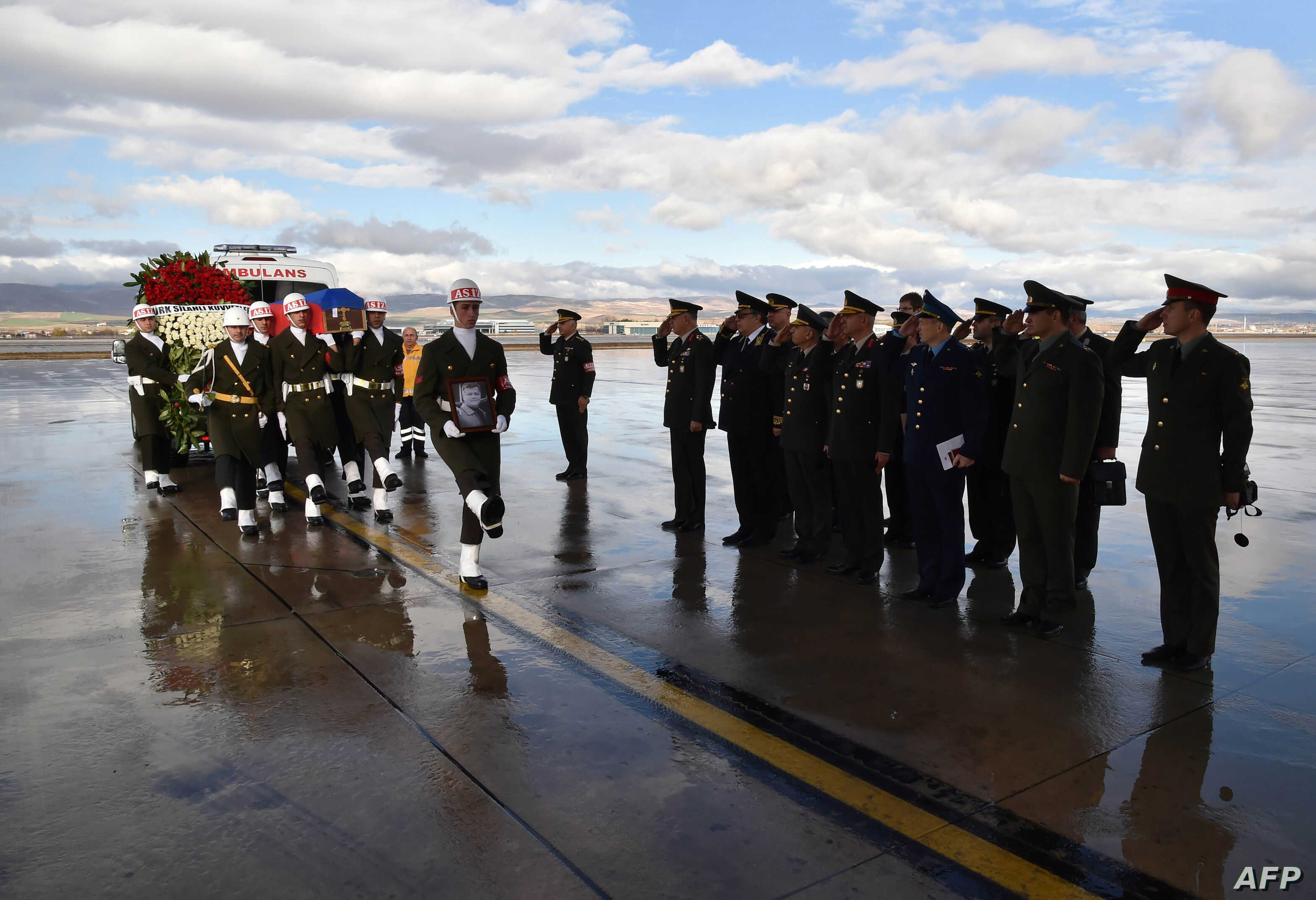 A picture released and taken on November 30, 2015 by Turkish army press office shows Turkish soldiers walking by officials of Russian army as they carry the coffin of Russian pilot Lt. Col. Oleg Peshkov into a Russian Air Force transport during a cer...