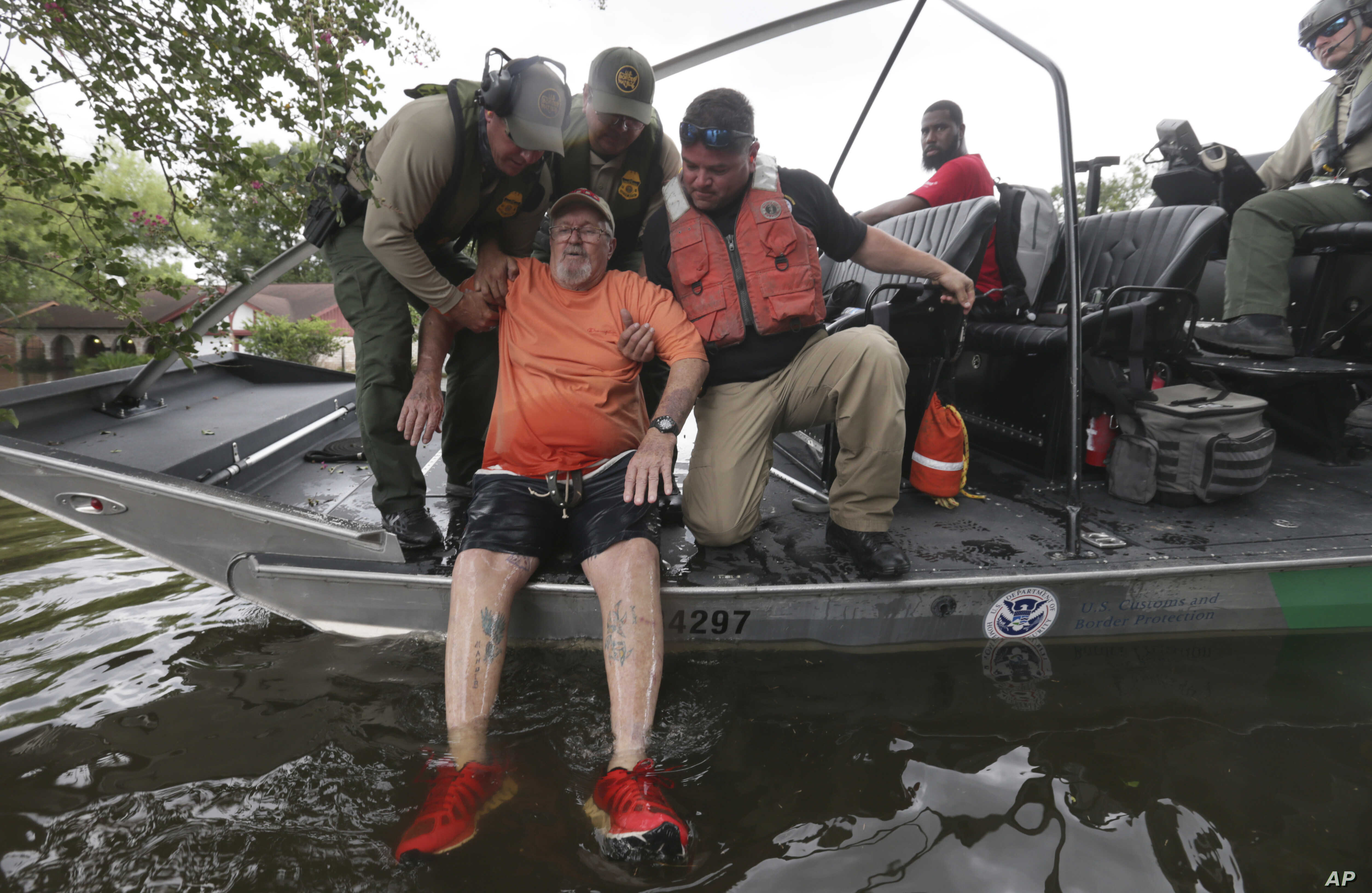 John Paul Klotz, 80, is pulled on a boat by U.S. Border Patrol Agents Steven Blackburn, left, Ramiro Rodriguez, top center, and Juan Flores during a search-and-rescue operation in a neighborhood inundated by floodwaters from Tropical Storm Harvey in ...